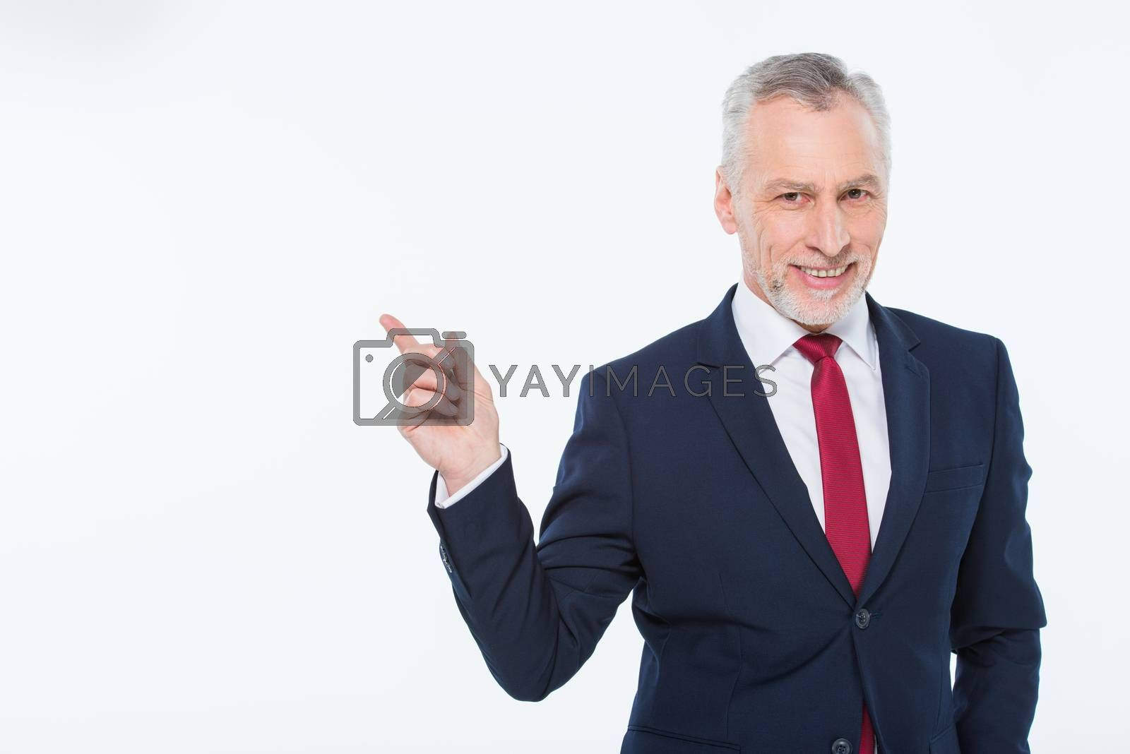 Handsome mature businessman pointing with finger at copy space