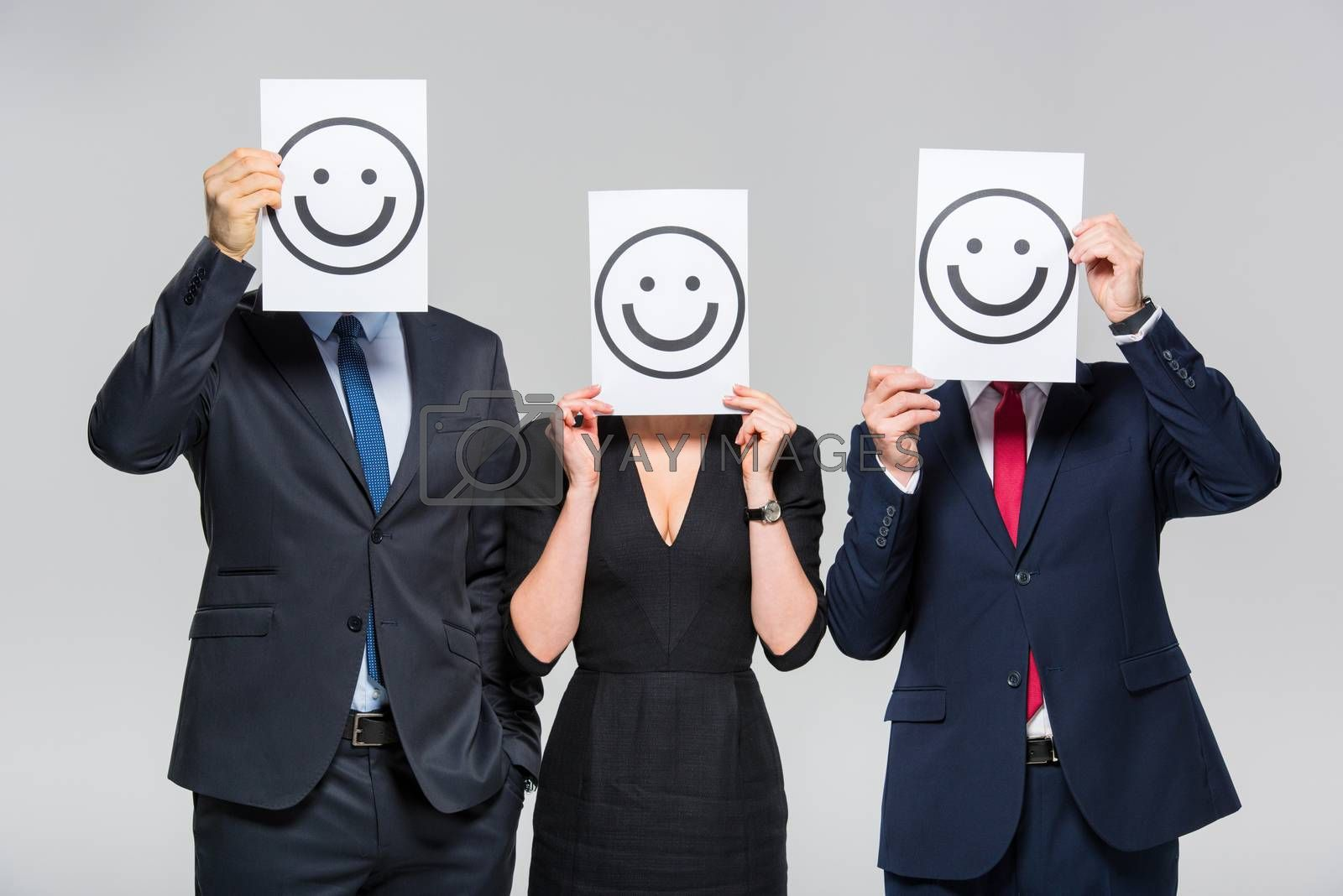 Three businesspeople holding cards with smileys on white