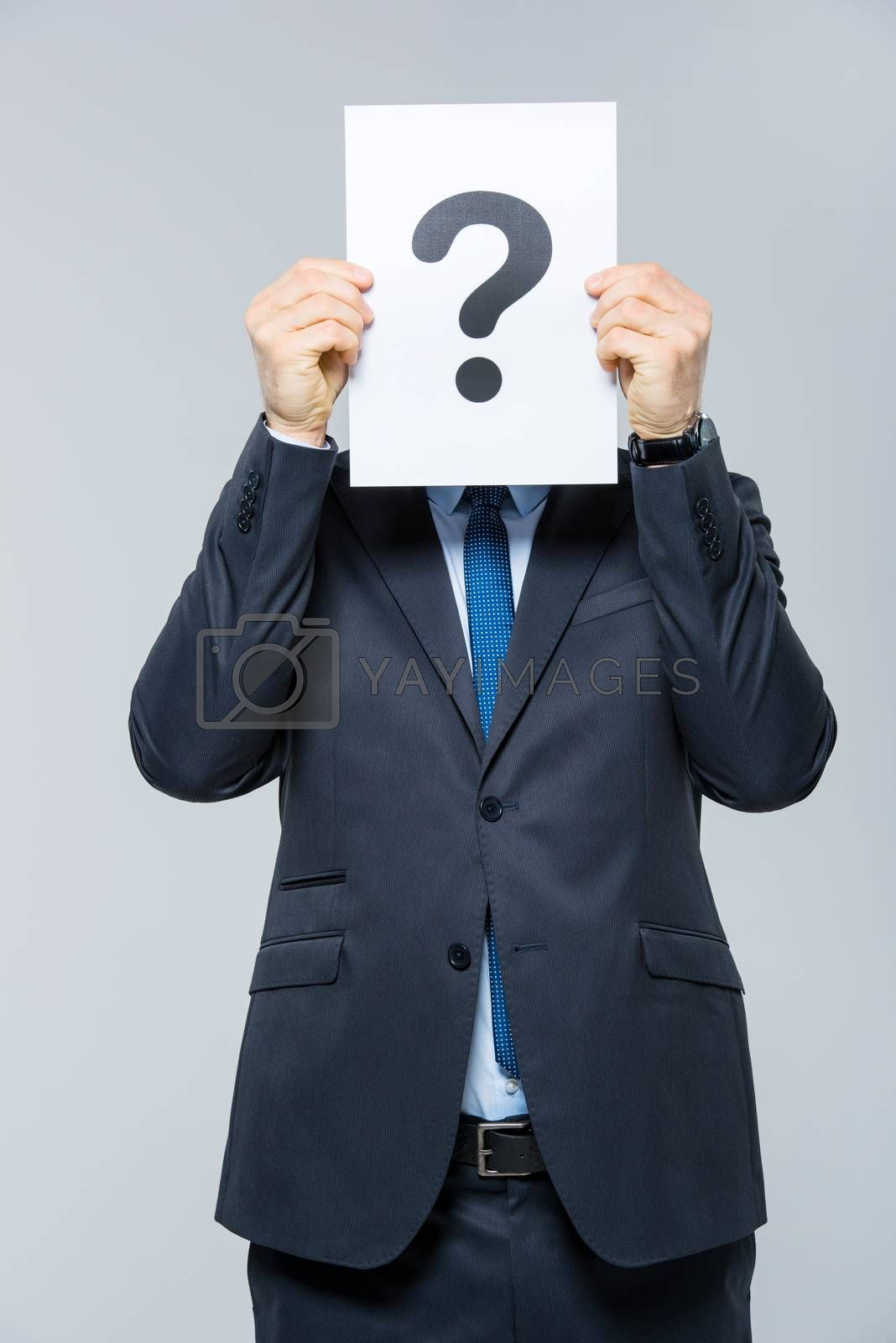 Businessman holding card with question mark and hiding his face behind it on white
