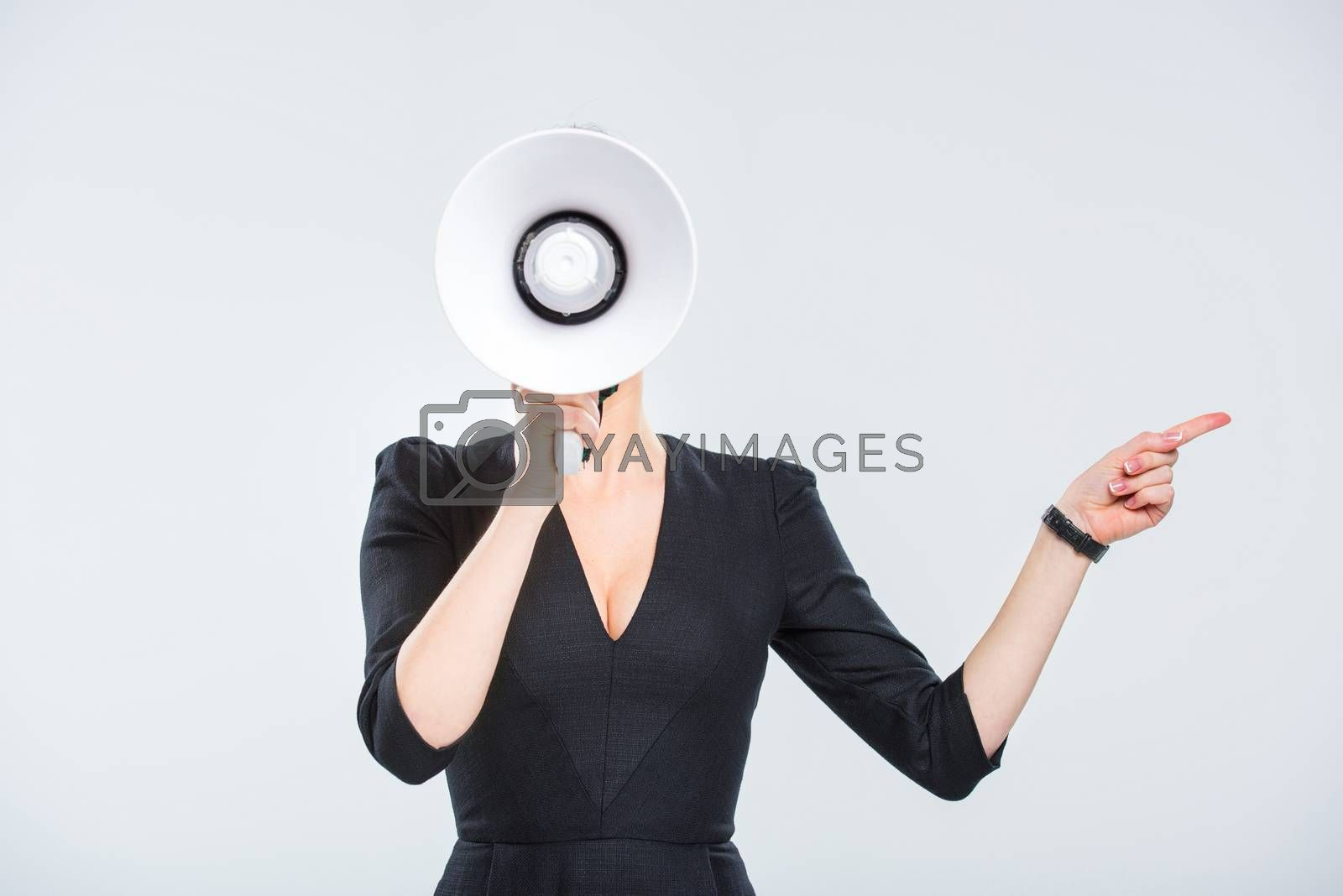 Young businesswoman with megaphone pointing to the side on white