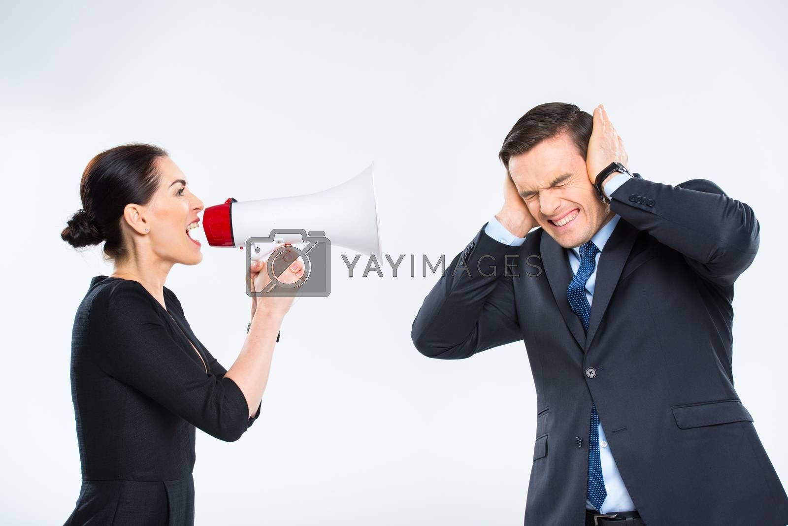 Young businesswoman screaming in megaphone at businessman on white