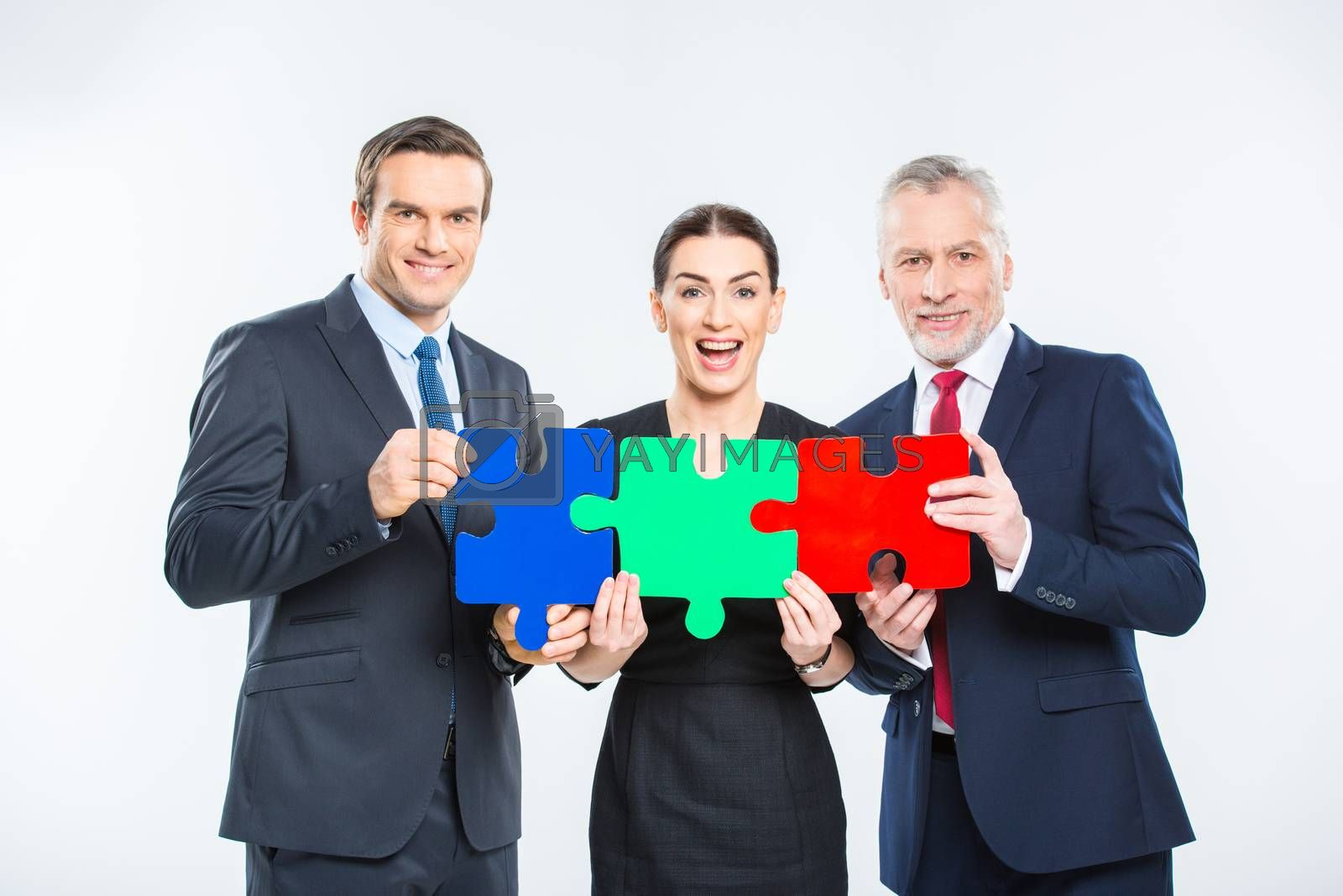 Three happy businesspeople holding puzzle pieces and looking at camera on white