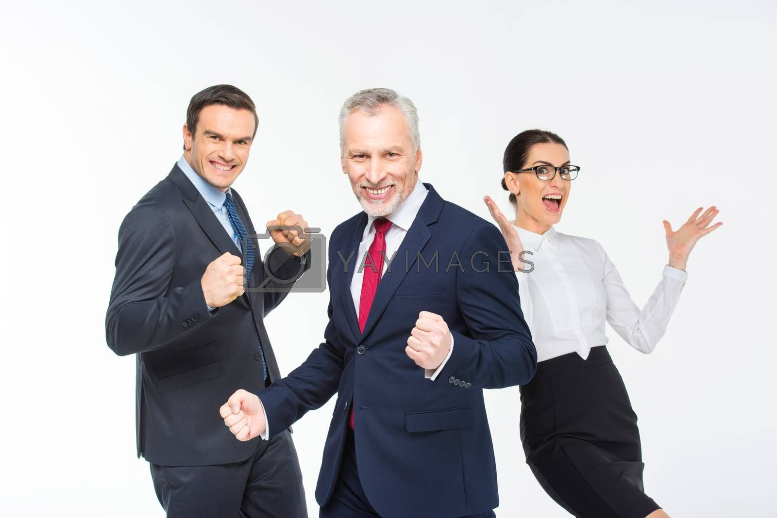 Three happy business people celebrating on white