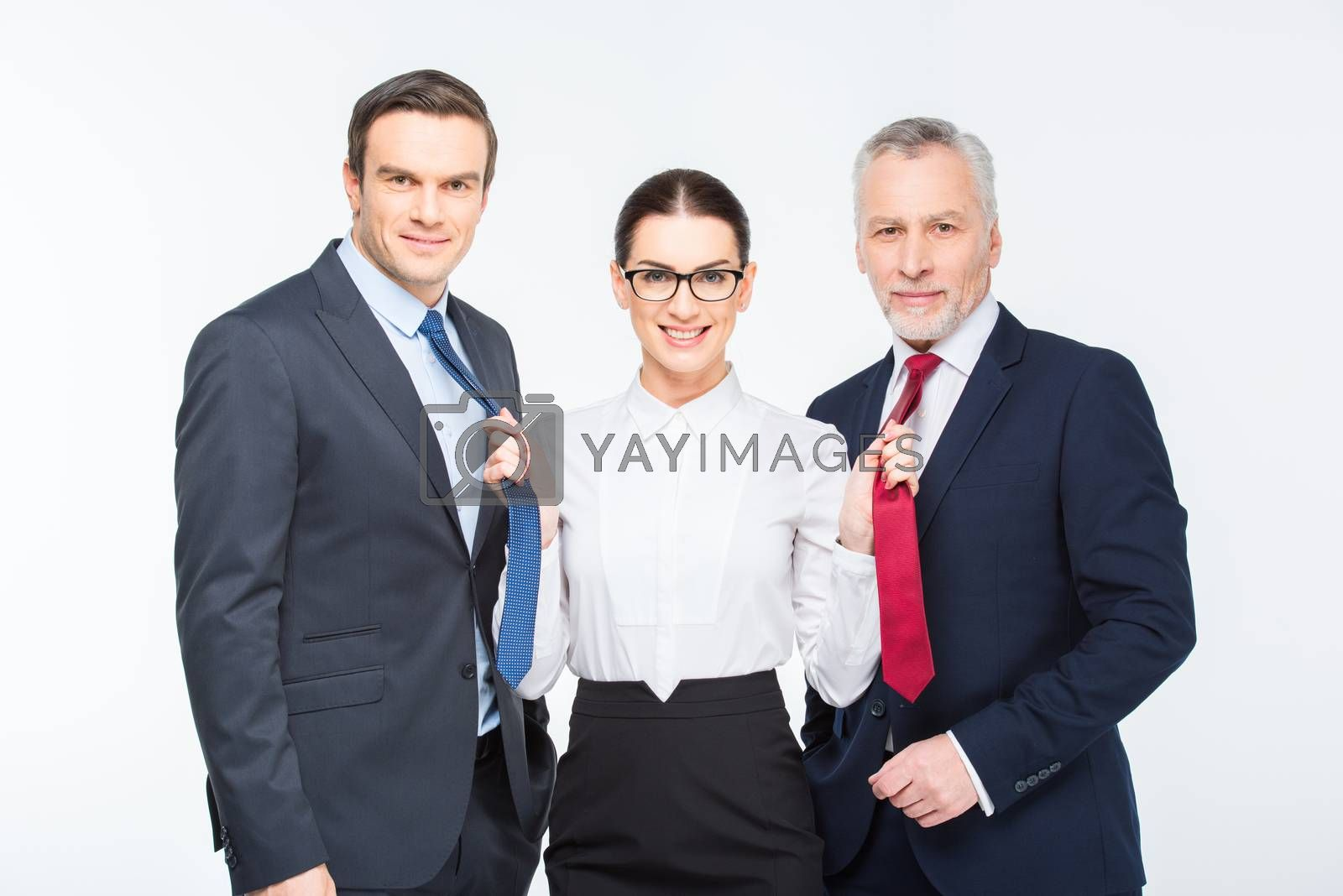 Three happy business people standing and woman holding neckties of businessmen on white
