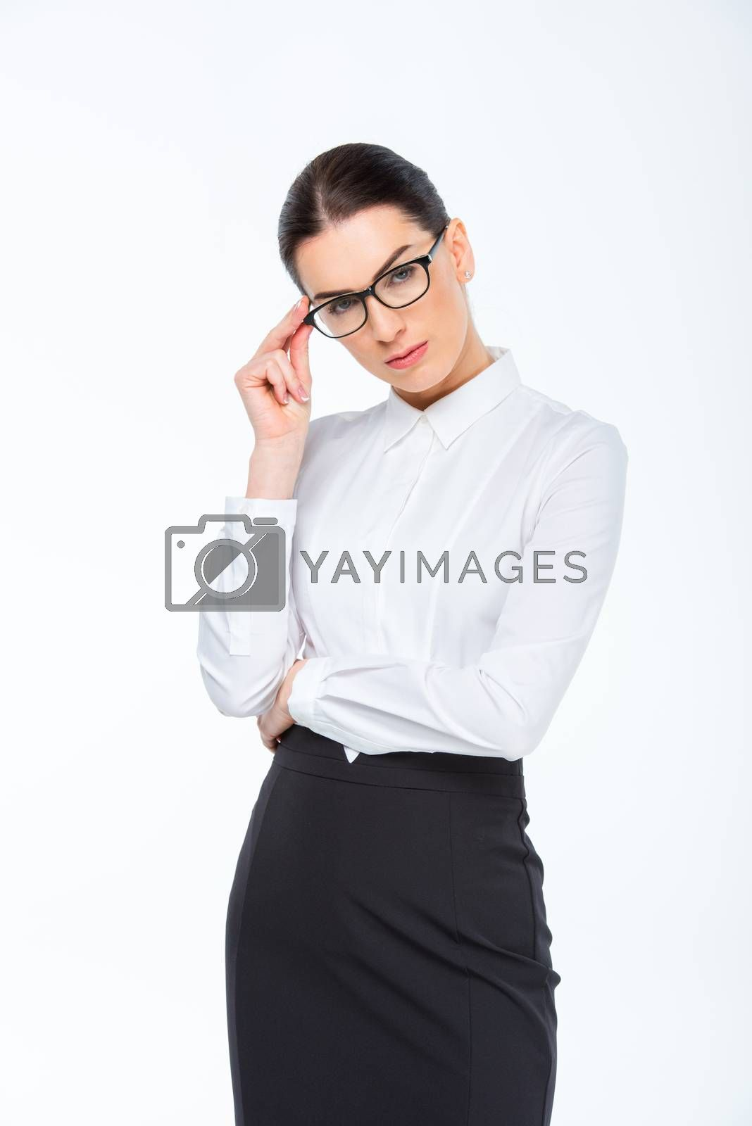 Confident young businesswoman in glasses looking at camera on white