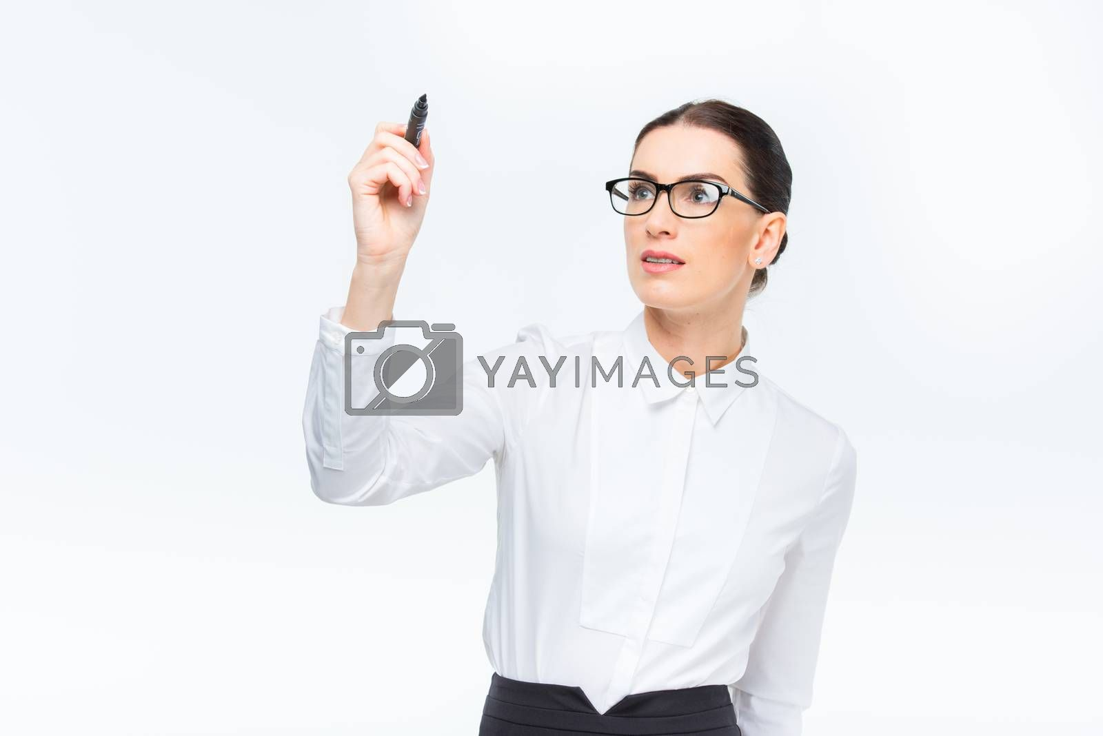 Young businesswoman in glasses writing with marker on white