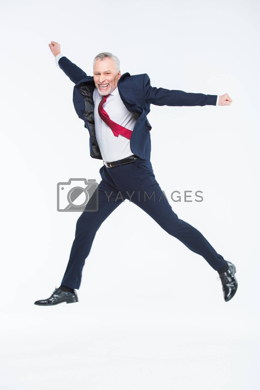 Happy mature businessman jumping on white