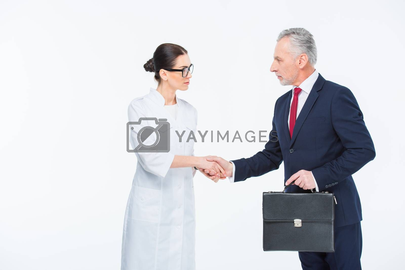 Businesspeople shaking hands by LightFieldStudios