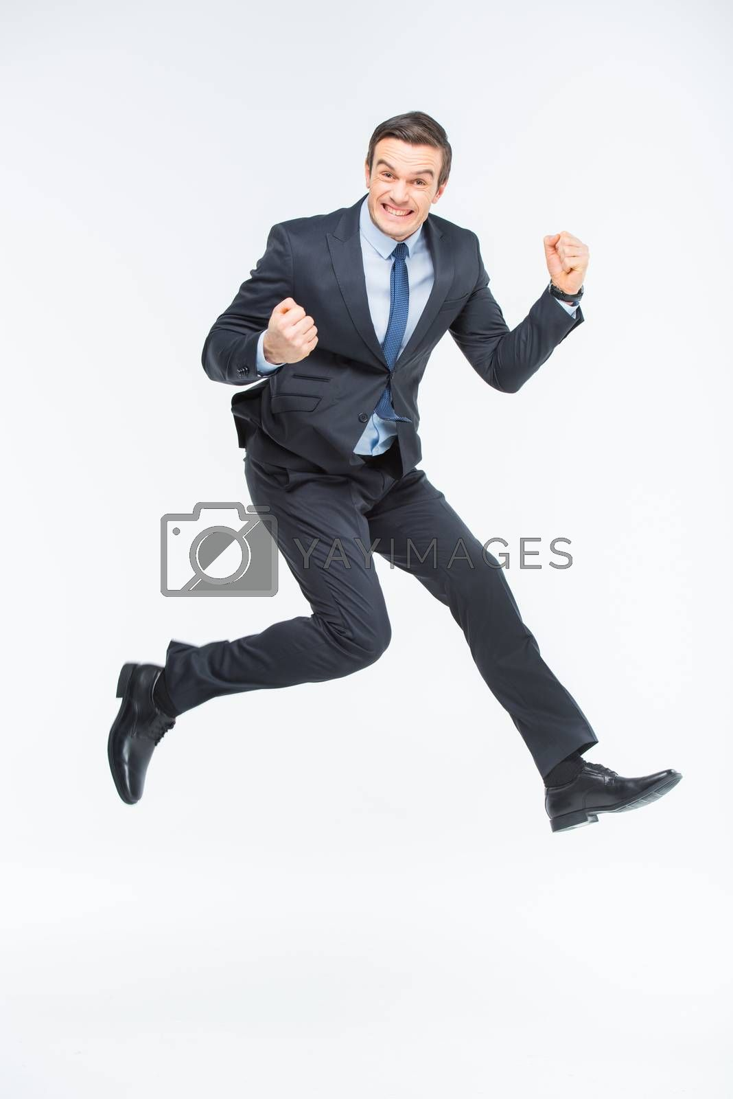 Young excited businessman jumping on white