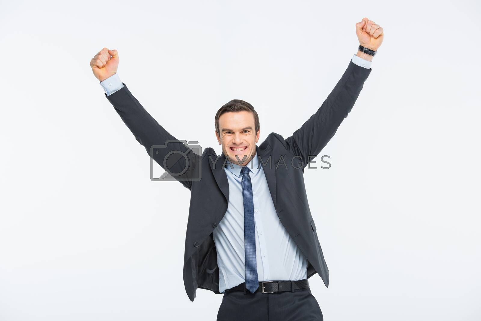 Young excited businessman rising hands on white