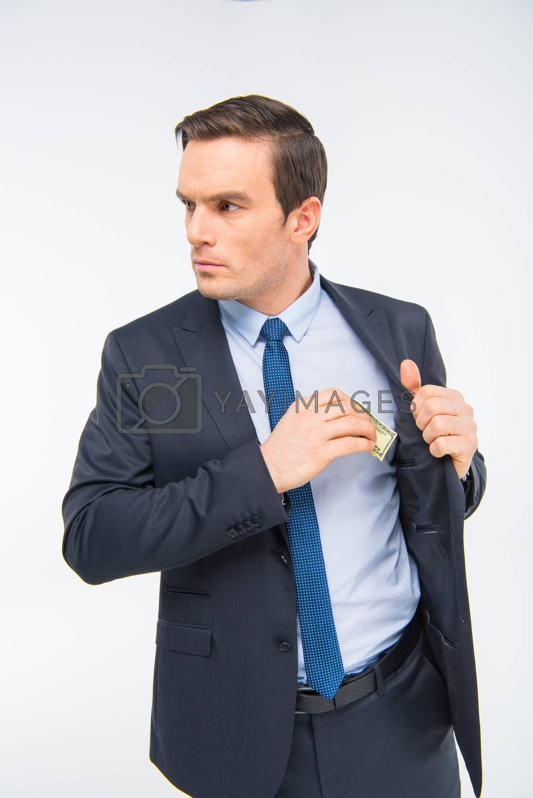 Young businessman hiding money in inner pocket of jacket on white