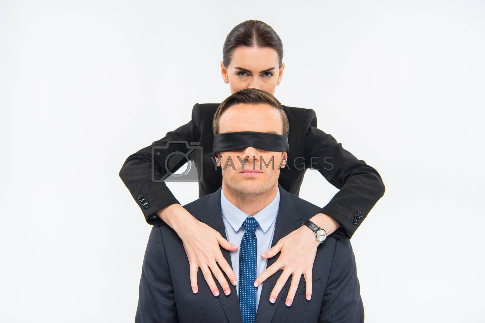 Young businesswoman holding hands on chest of businessman in blindfold on white