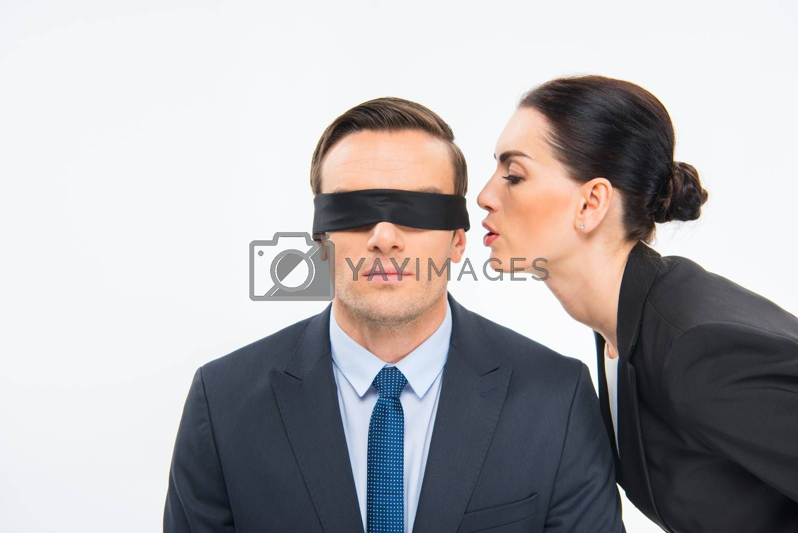 Young businesswoman whispering in the ear of businessman in blindfold on white