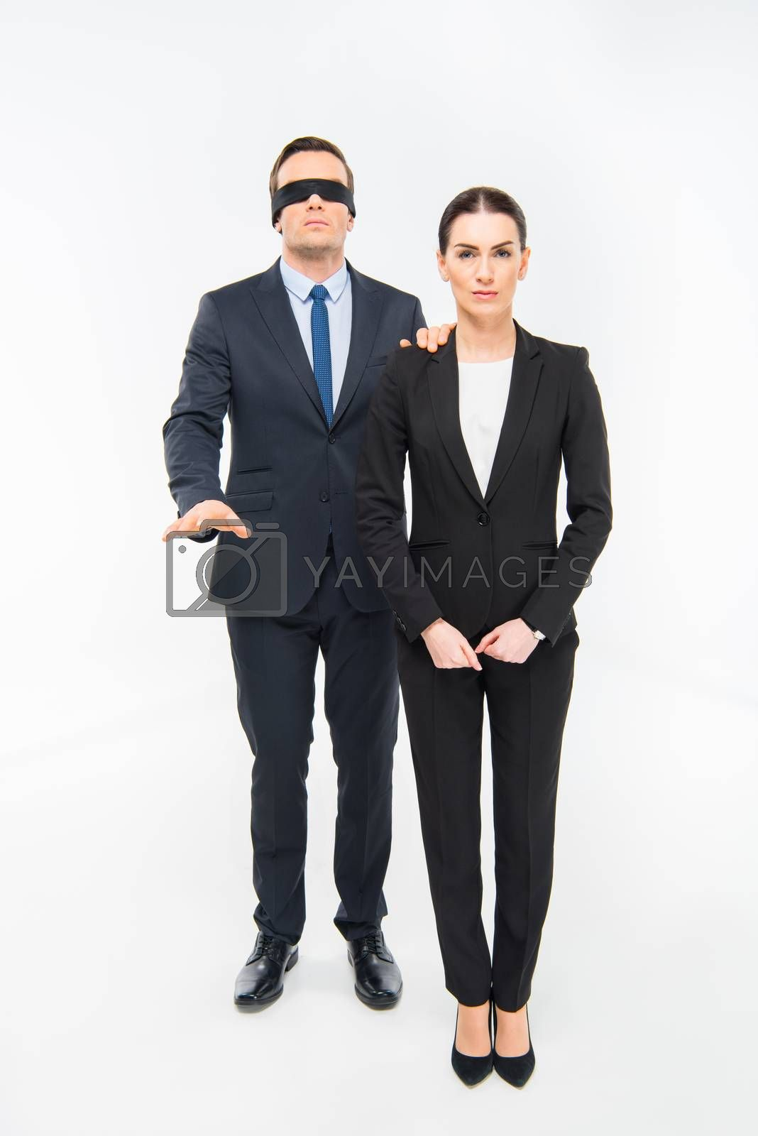 Businessman in blindfold holding his hand on shoulder of businesswoman on white