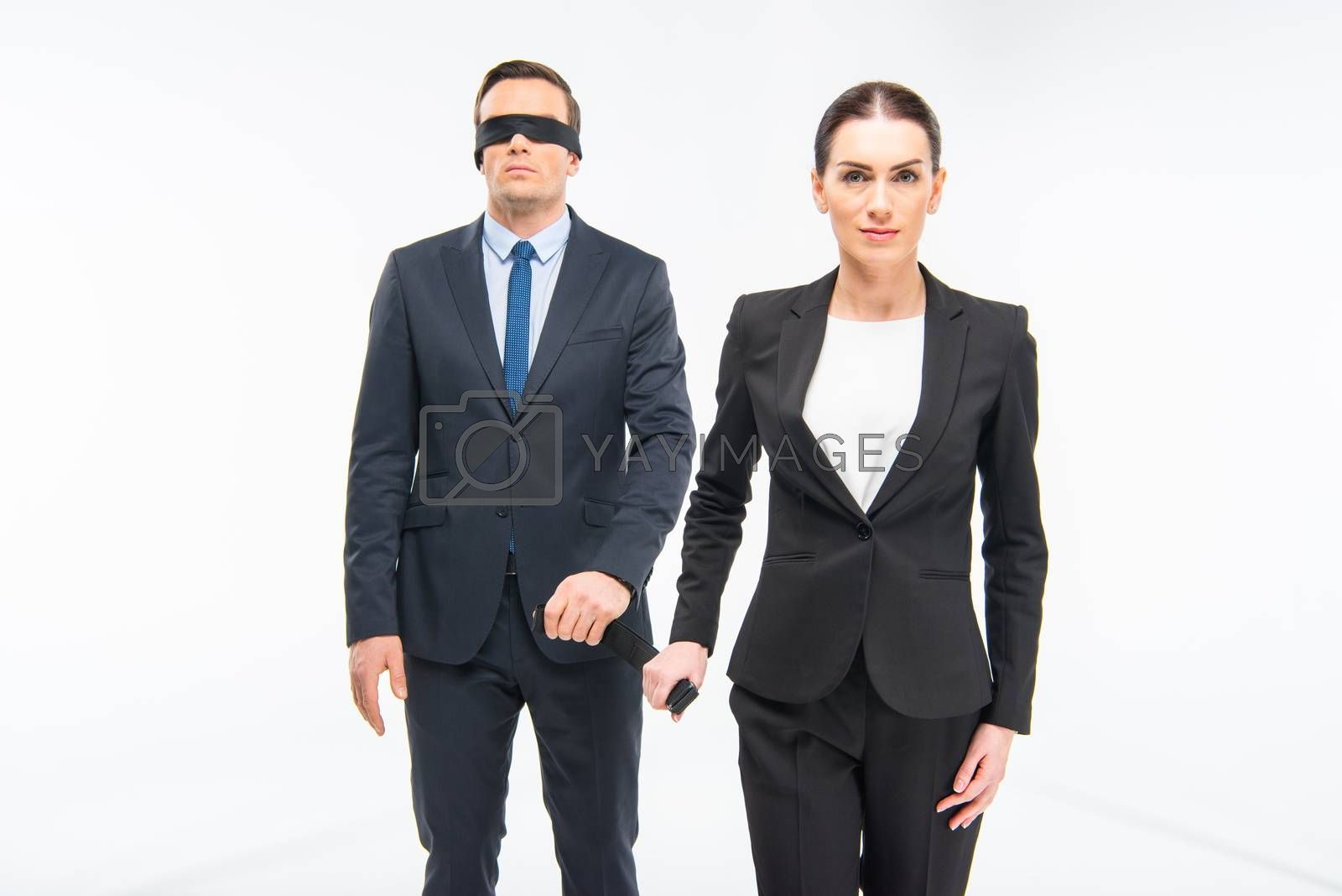 Young businesswoman leading businessman in blindfold on white