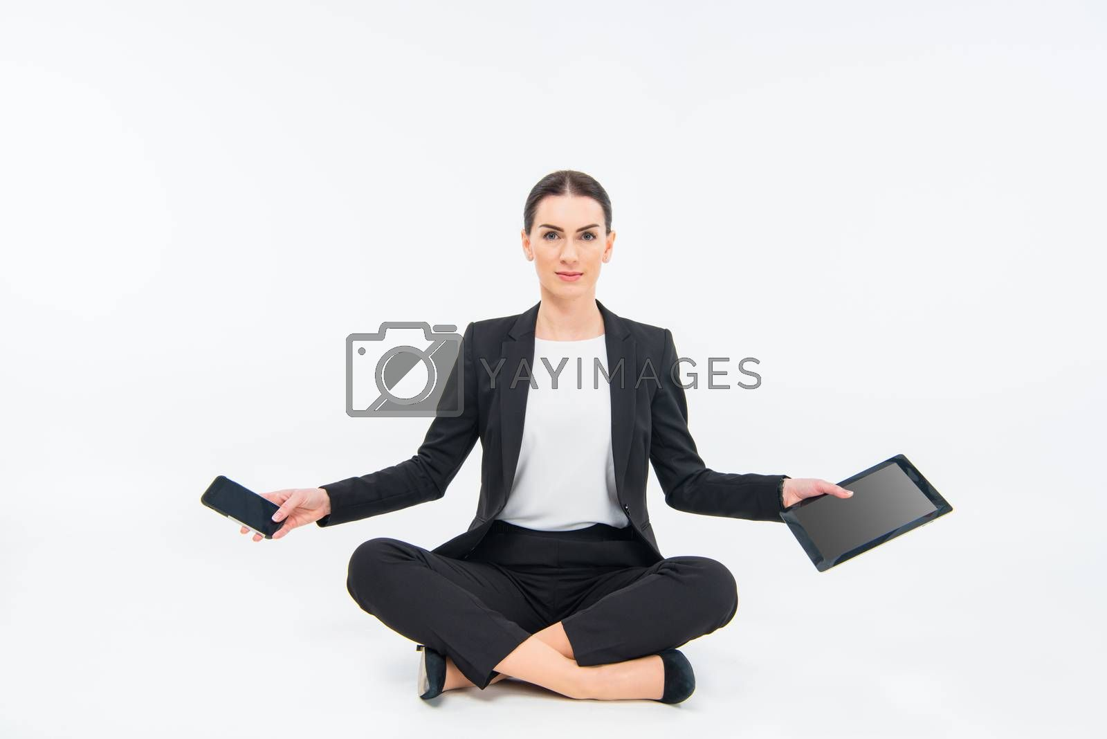 Young businesswoman sitting on floor and holding tablet computer and smartphone on white