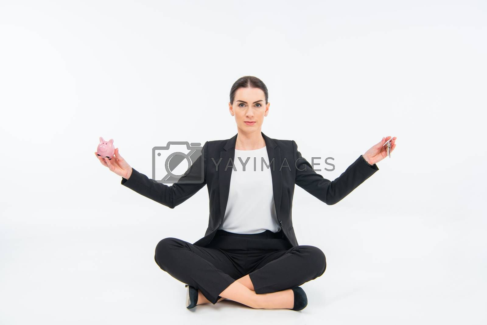 Young businesswoman sitting on floor and holding piggy bank and keys on white