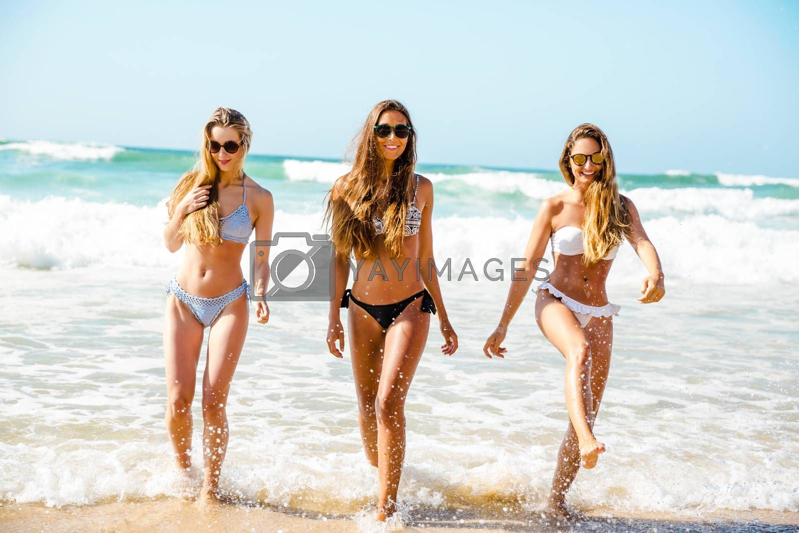 Beautiful girls in the beach having fun on the water