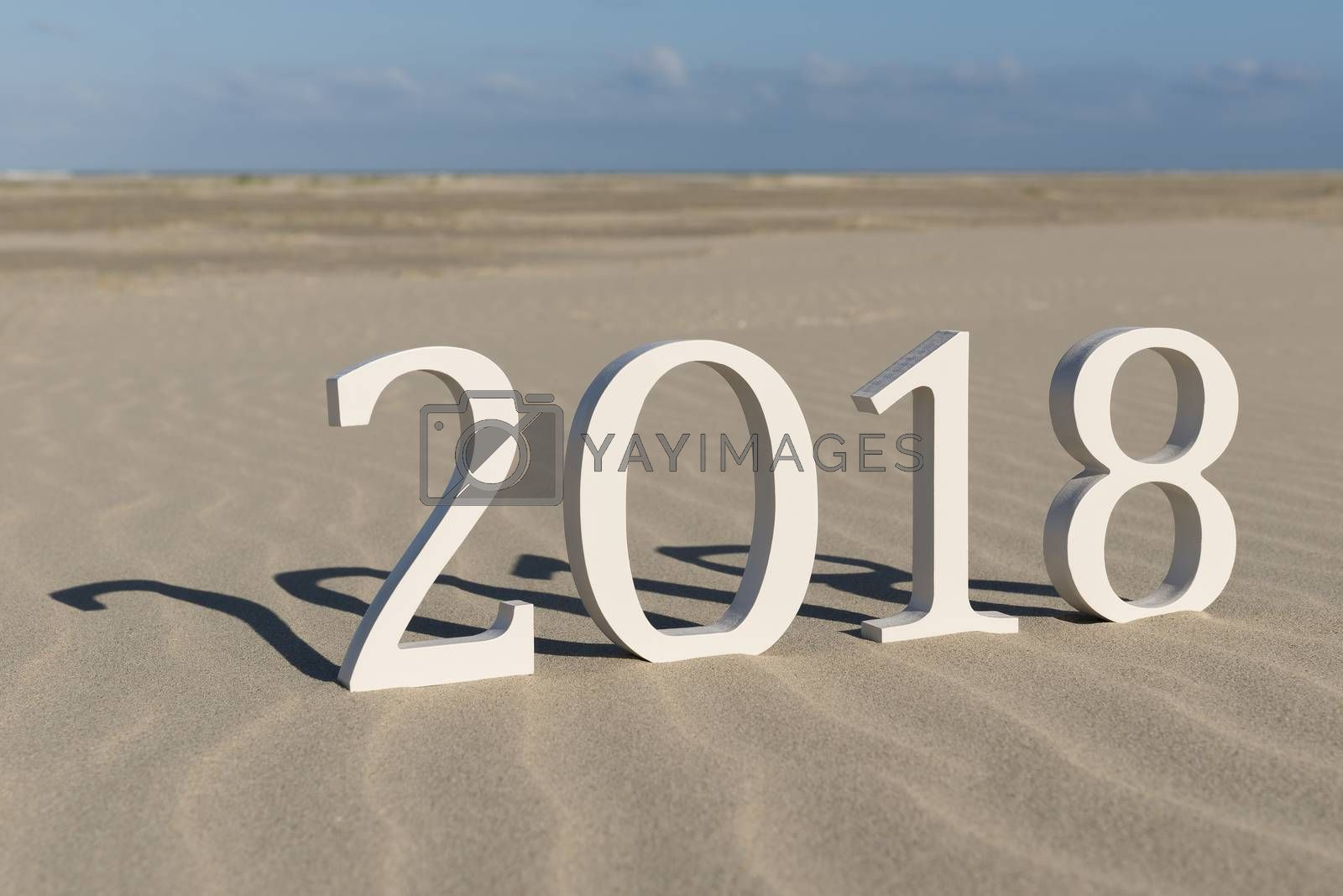 White wood figures on a beach forming the text two thousand eighteen as conceptual welcoming of the coming new year