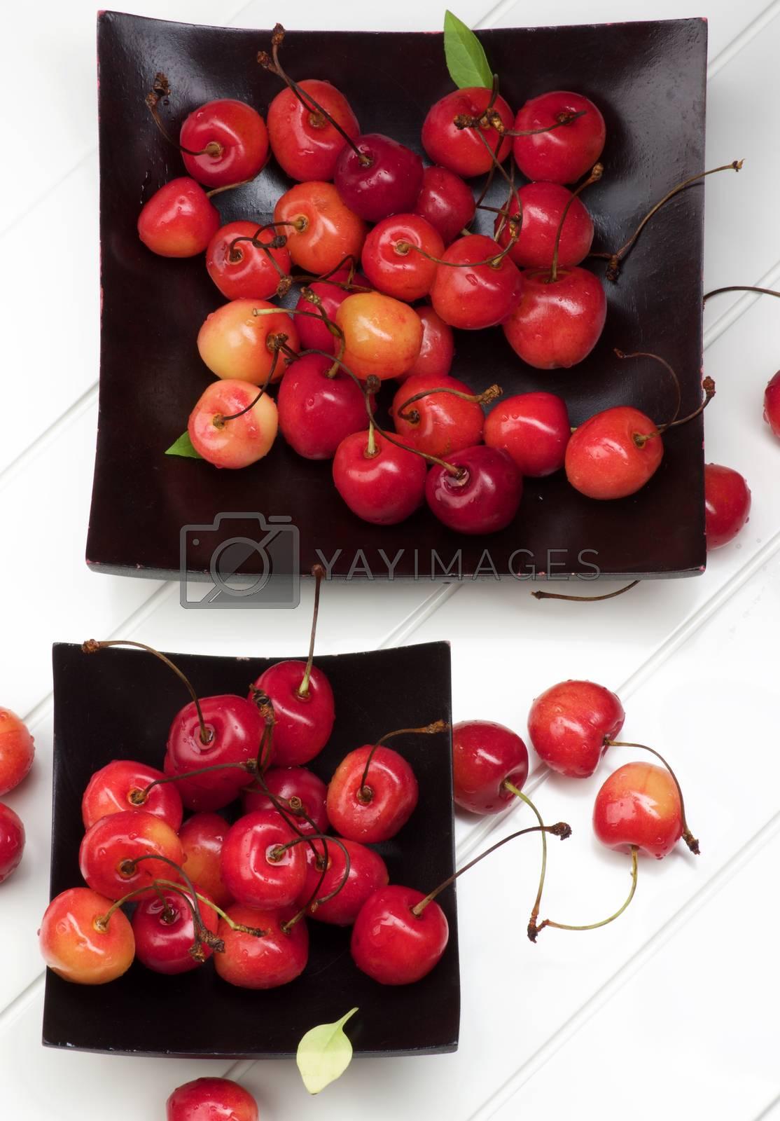 Arrangement of Two Black Plates Full of Fresh Ripe Sweet Maraschino Cherries closeup on Plank White background