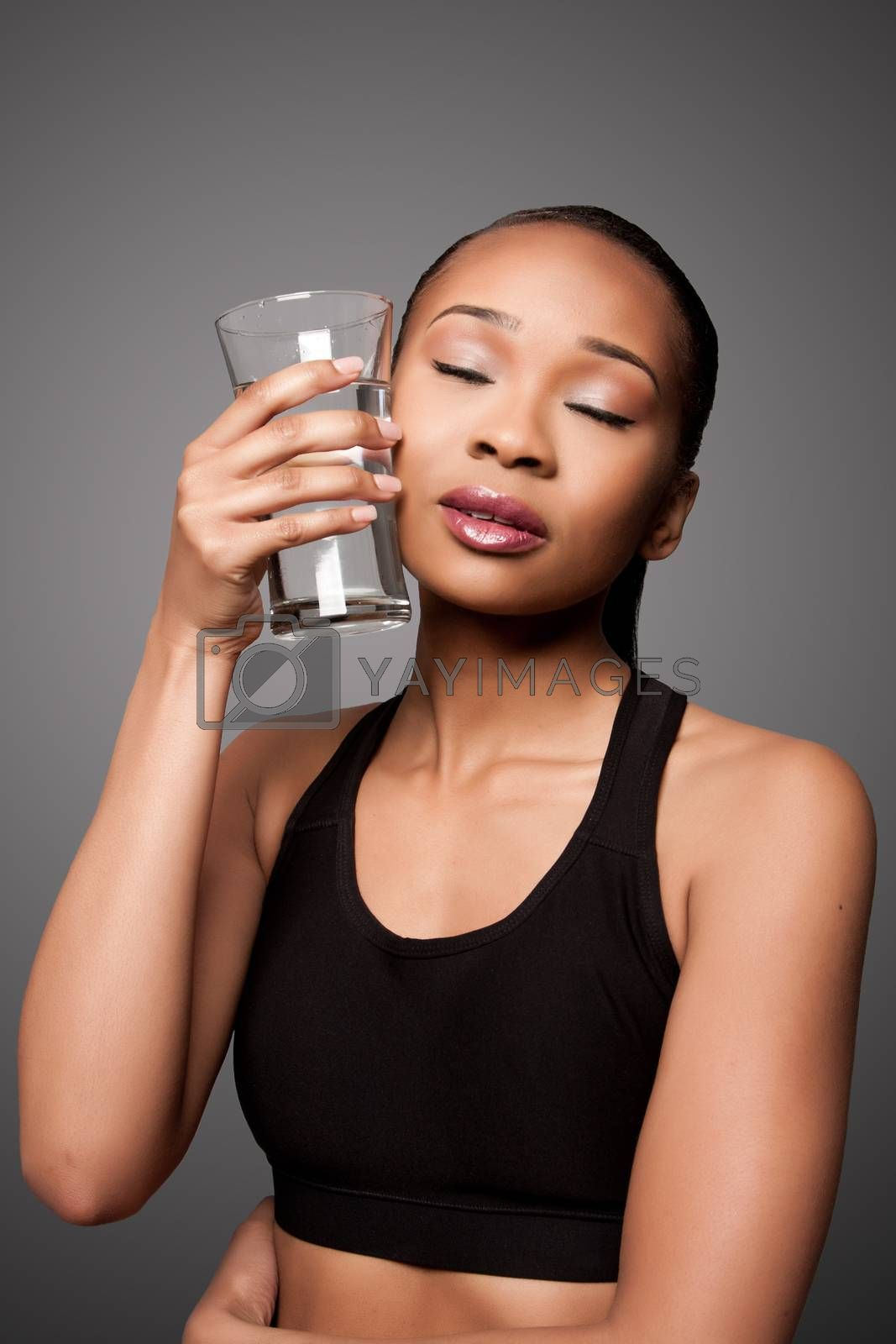 Beautiful healthy black asian woman with glass of water cooling off after workout.