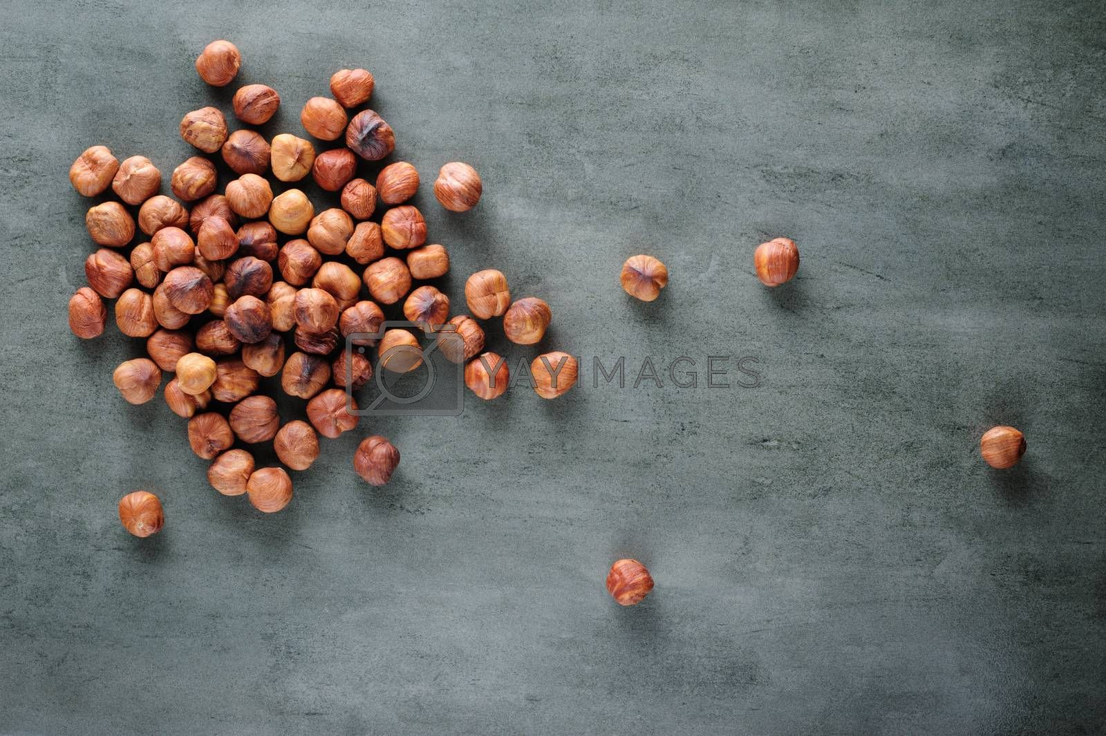 Peeled hazelnuts scattered over stone board, copy space