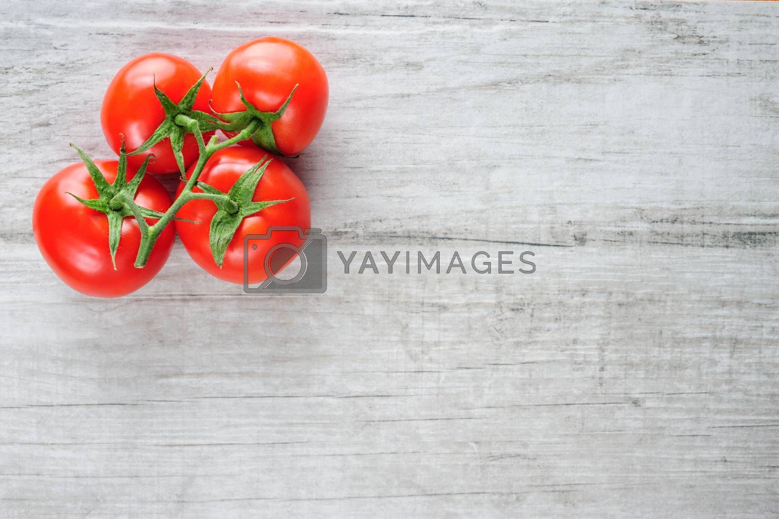 Top view of bunch of fresh tomatoes on lwhite wooden board