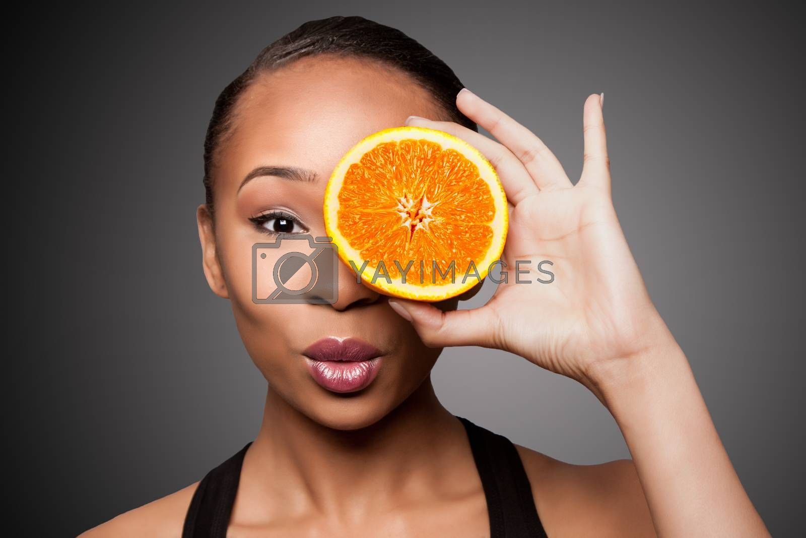 Beautiful healthy happy black asian woman holding delicious orange mandarin fruit in front of eye.