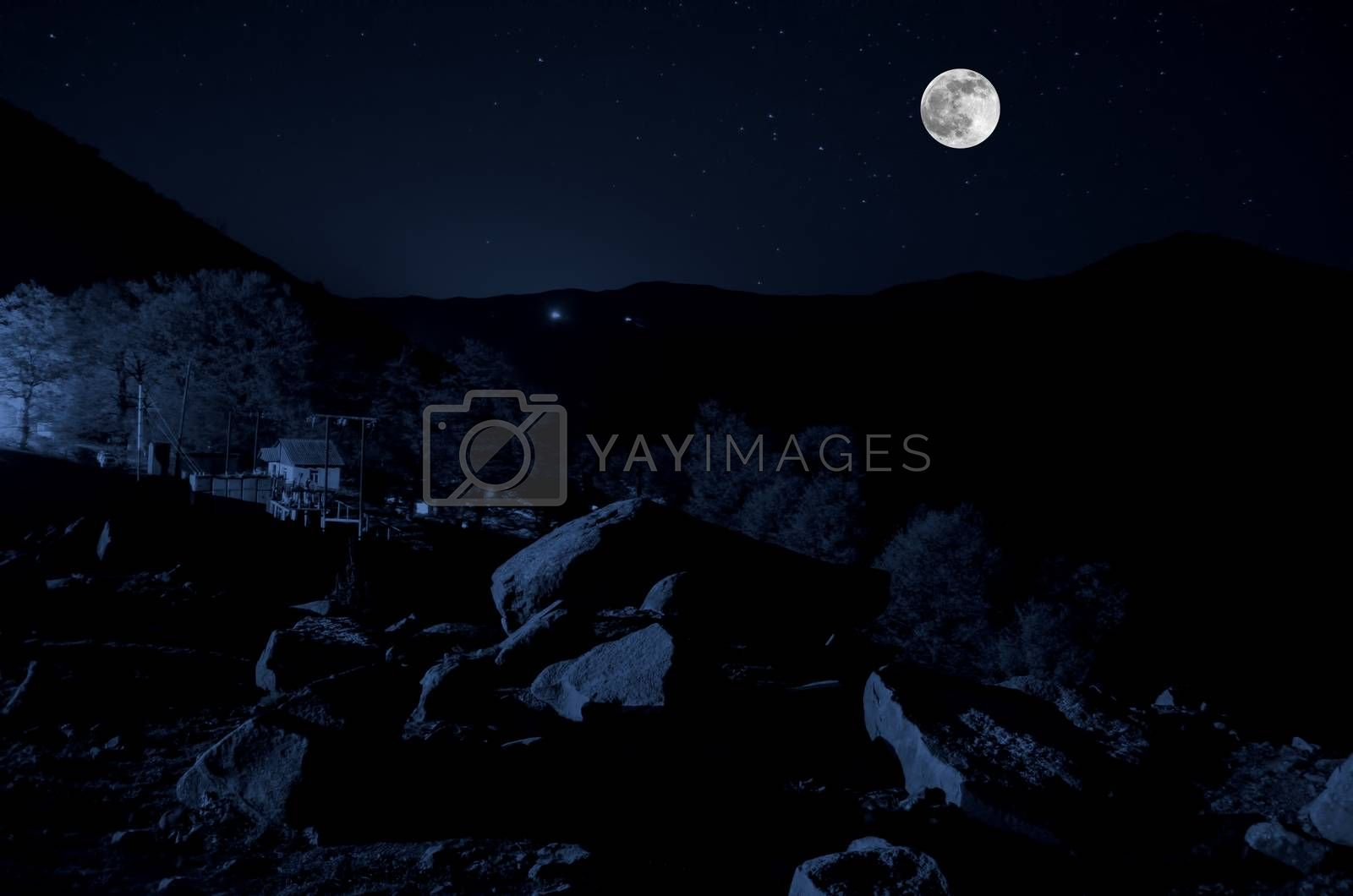 Beautiful night view of bright magical moon with dark blue clouds under the hills. Azerbaijan