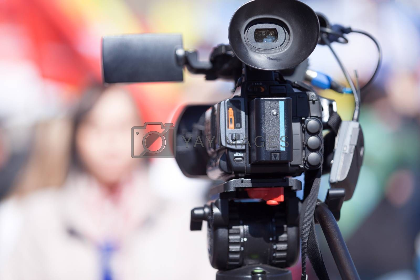 Television camera in the focus, blurred female journalist in the background. TV broadcasting.