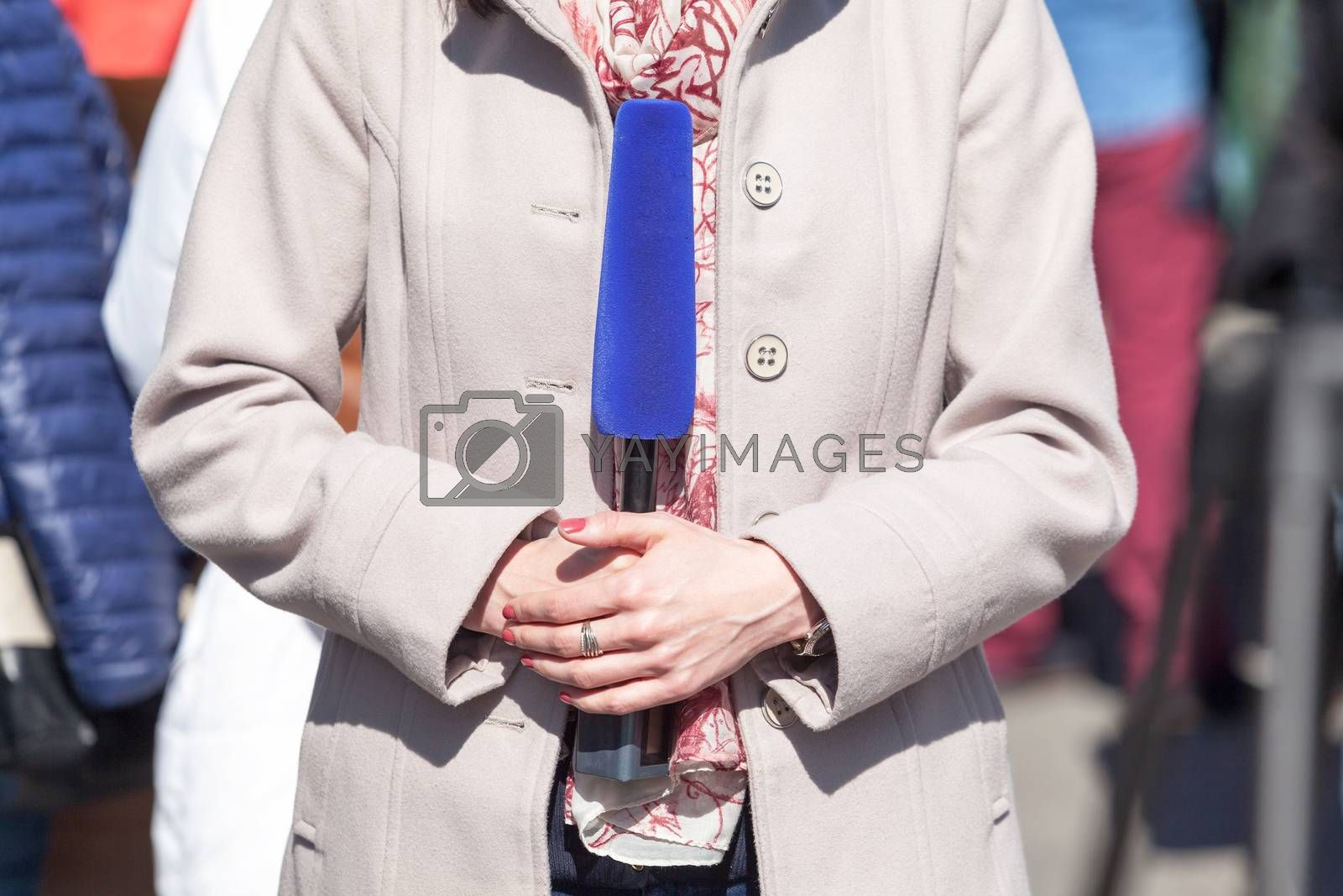 Female reporter holding microphone, making a media report