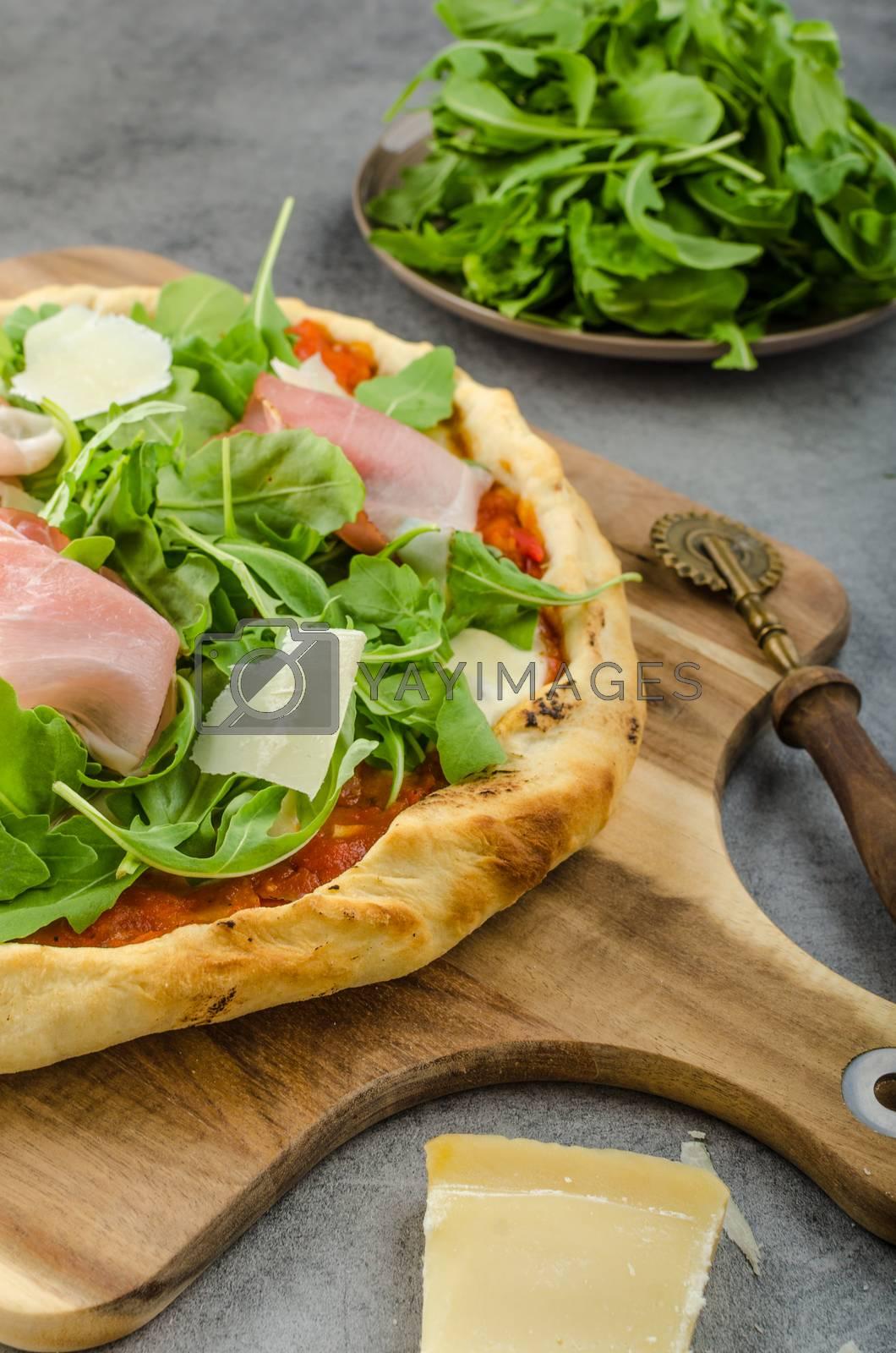 Rustic pizza with arugula, Parma ham and Parmesan
