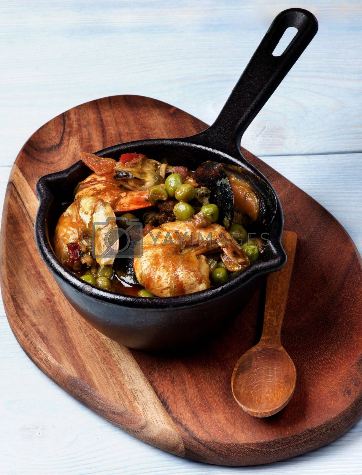 Delicious Seafood Curry with Prawns, White Fish, Mussels and Vegetables in Black Iron Cast Pot with Wooden Spoon closeup on Serving Board