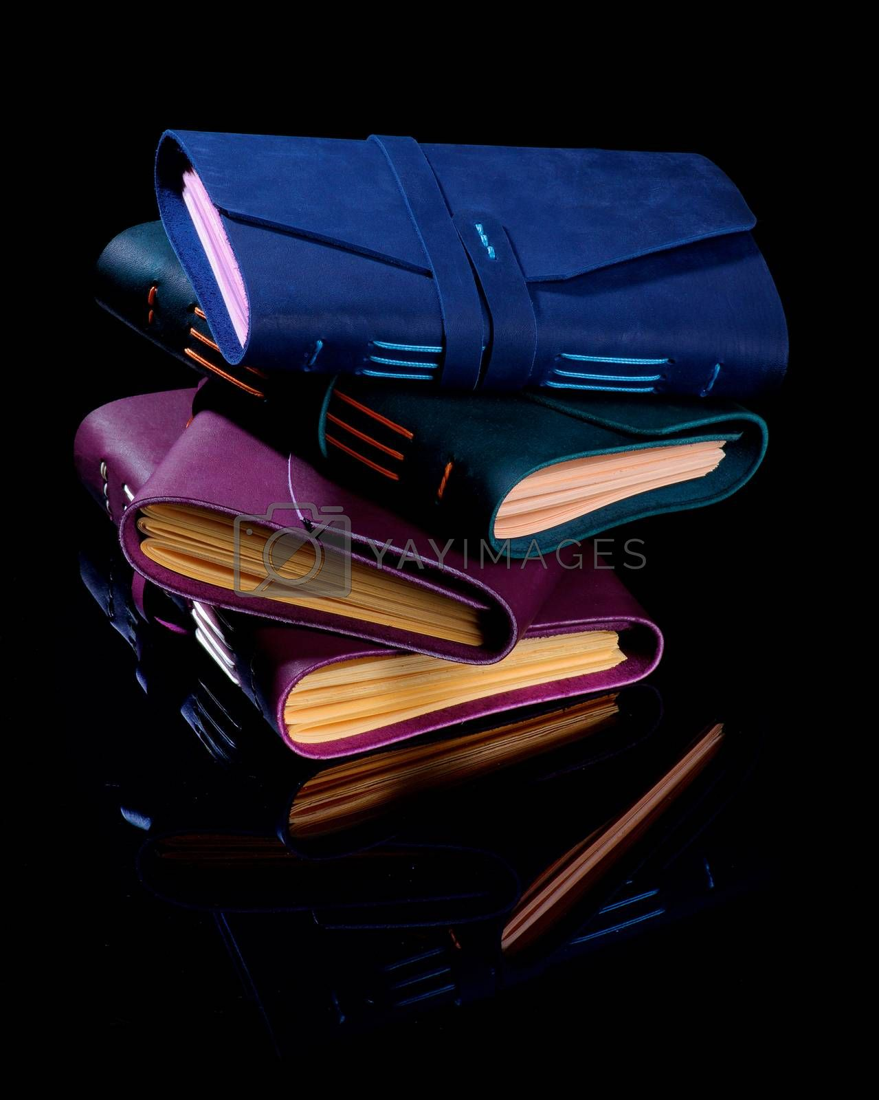 Stack of Luxury Handmade Leather Notepads with color Craft Paper isolated on Black background