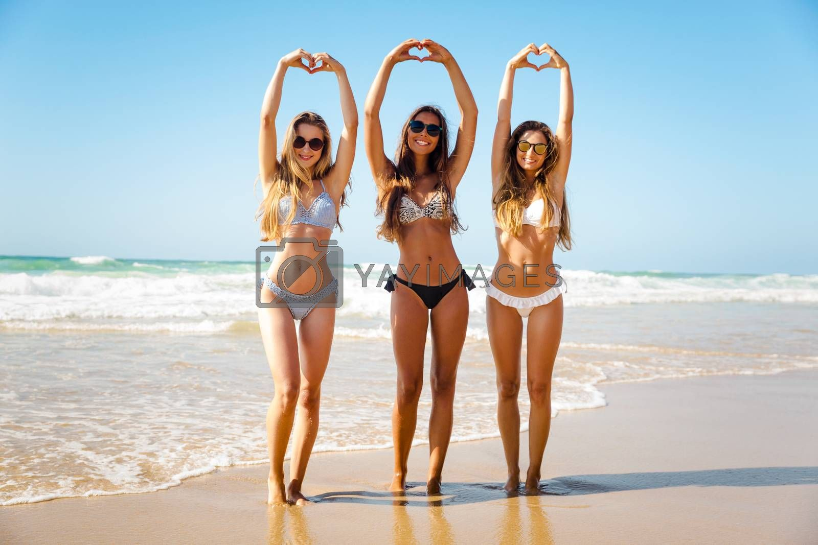 Beautiful girls in the beach making hearts with their hands