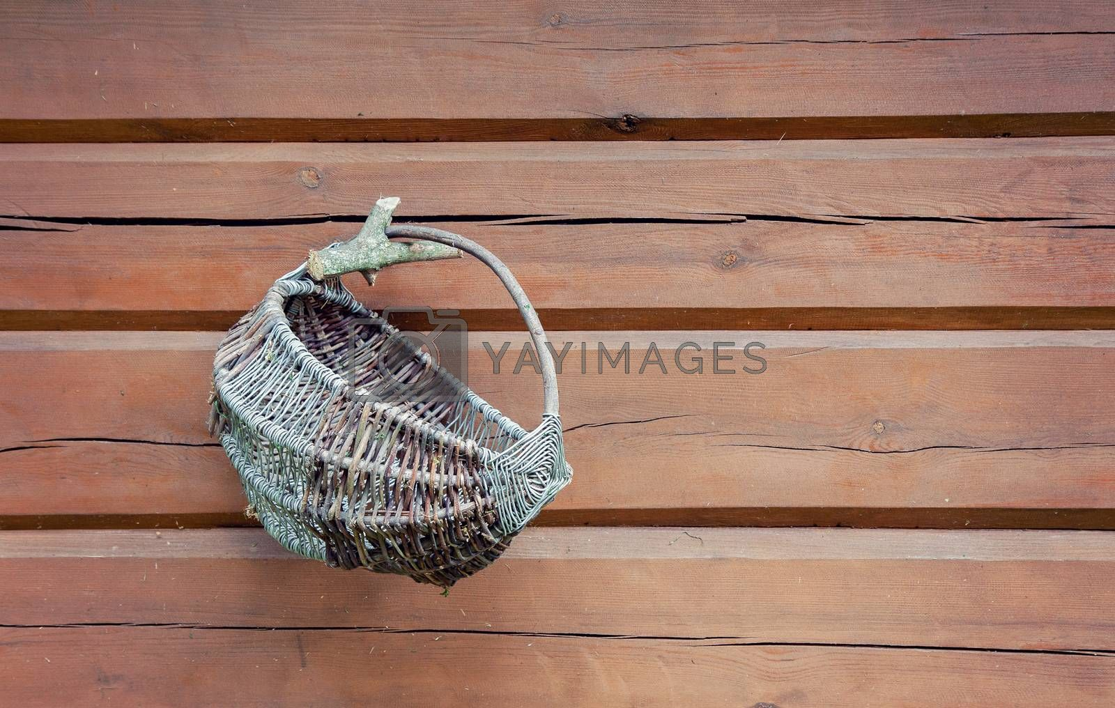 Old wicker basket hanging on wooden wall with plenty of copy space