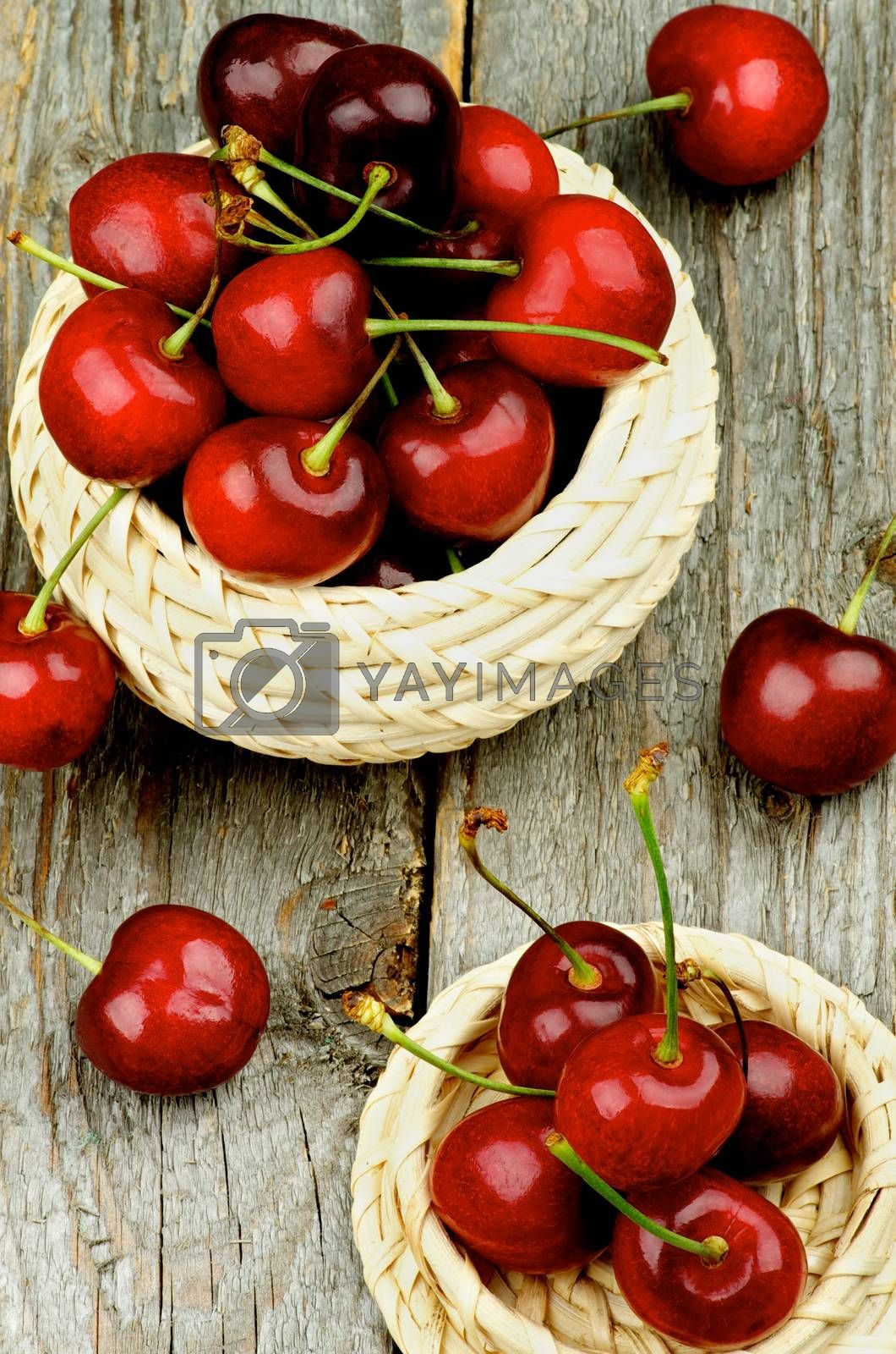 Ripe Red Sweet Cherries with Stems in Wicker Bowls closeup on Rustic Wooden background. Top View