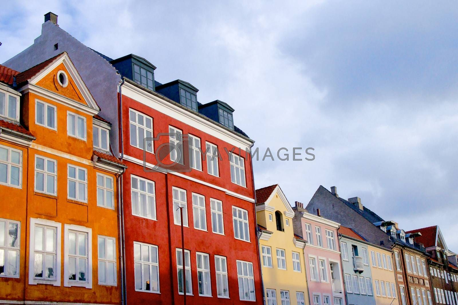 Wall of Colorful Houses with Attic Windows against Blue Sky Outdoors. Copenhagen, Denmark
