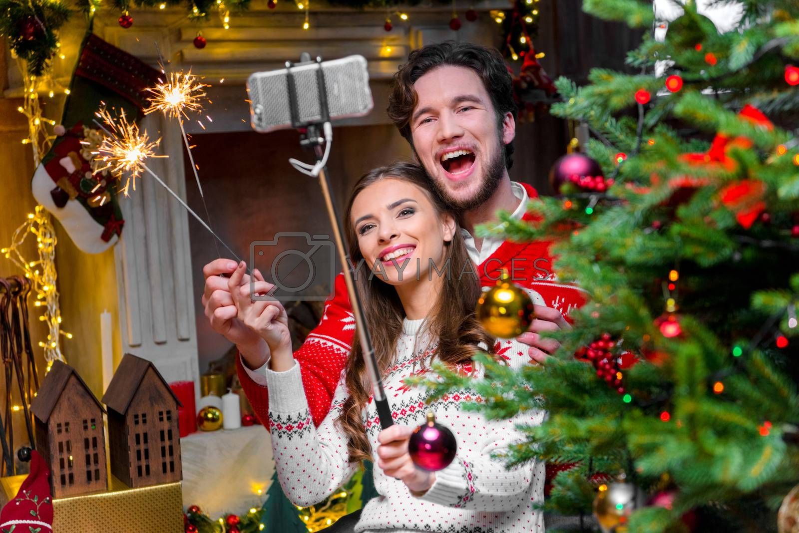 Happy young couple taking selfie with sparklers near the Christmas tree