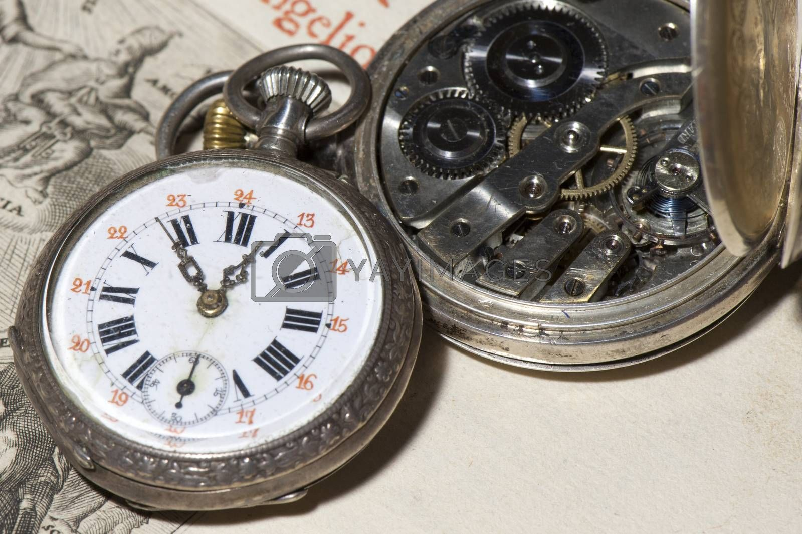 antique pocket watch on ancient Bible into Latin