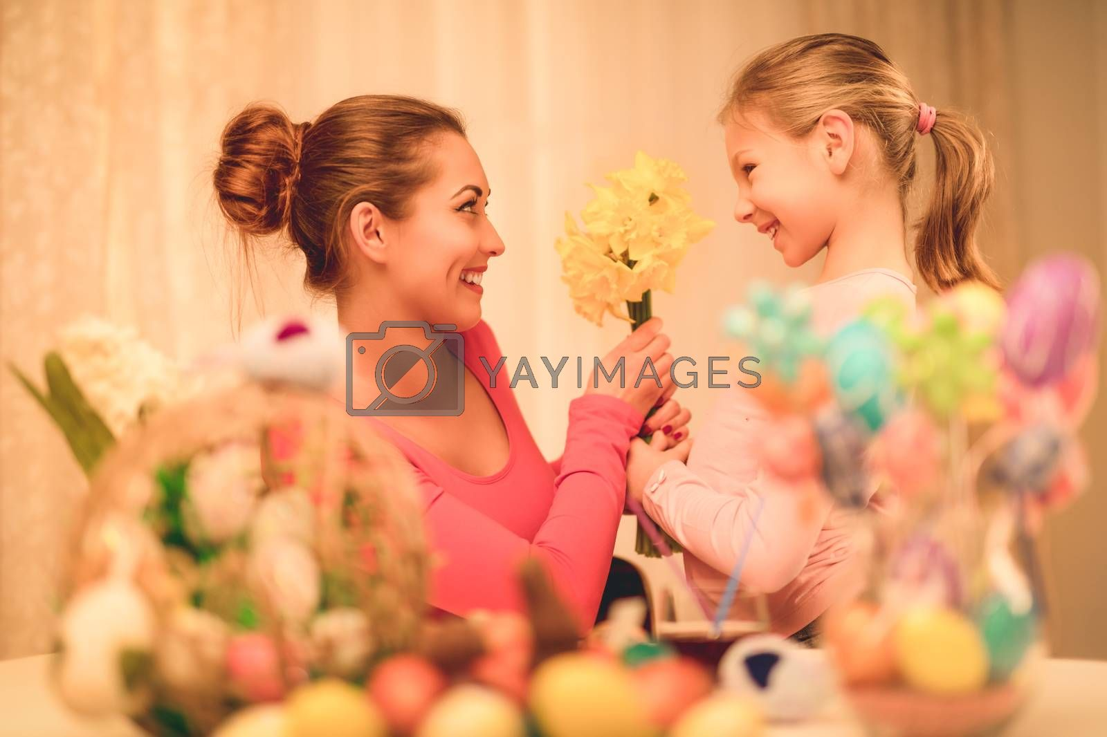Cute little girl giving her mother bouquet yellow daffodils.