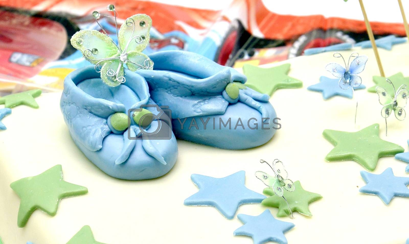 Celebrating baby boy first birthday, cute sweet shoes on a cake