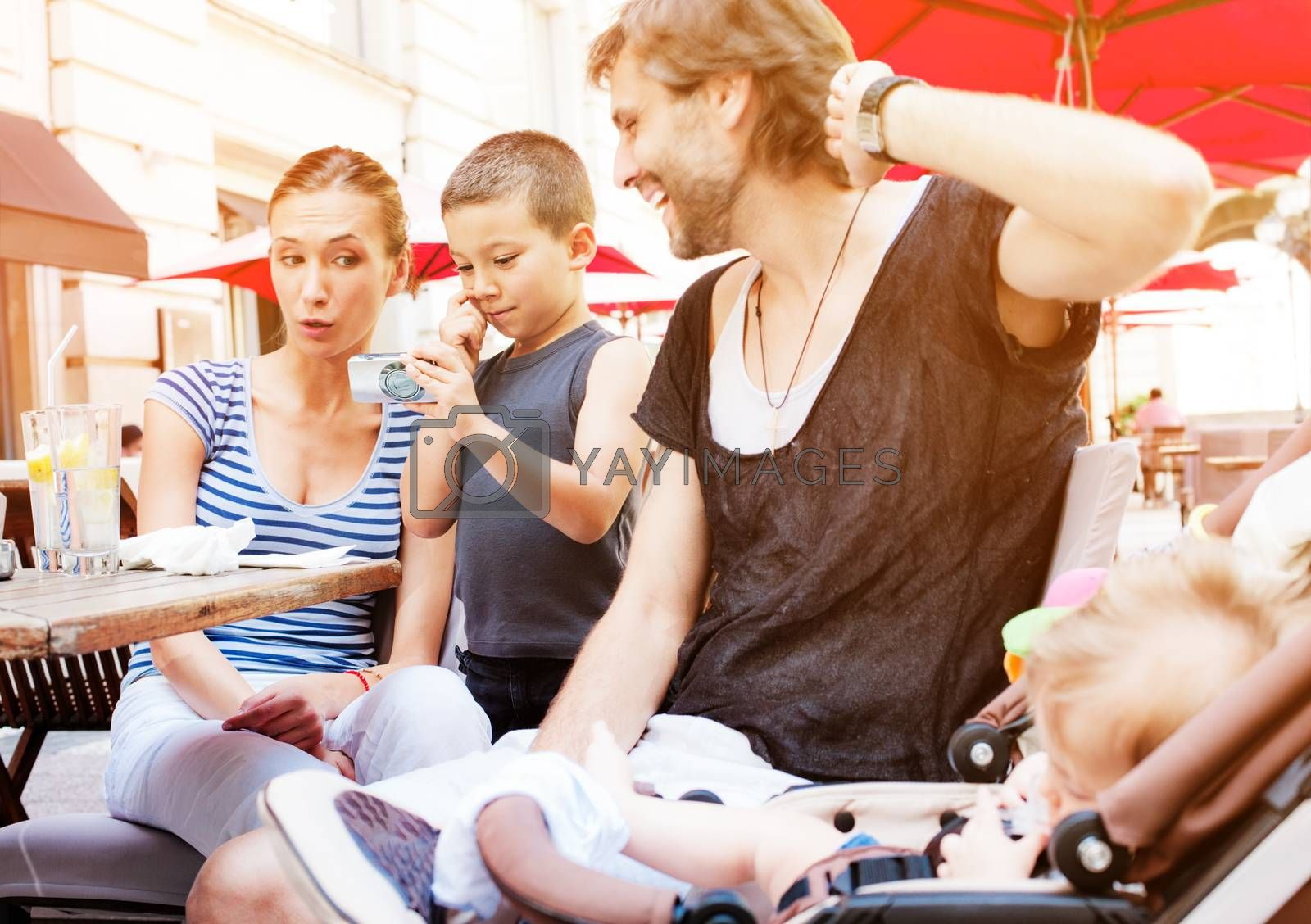 A young boy is showing pictures on camera to his parents in a warm summer day at an outdoor cafe.