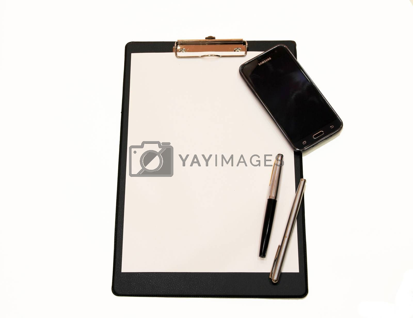 A sheet of paper with a pen and smartphone on white background by mdsfotograf