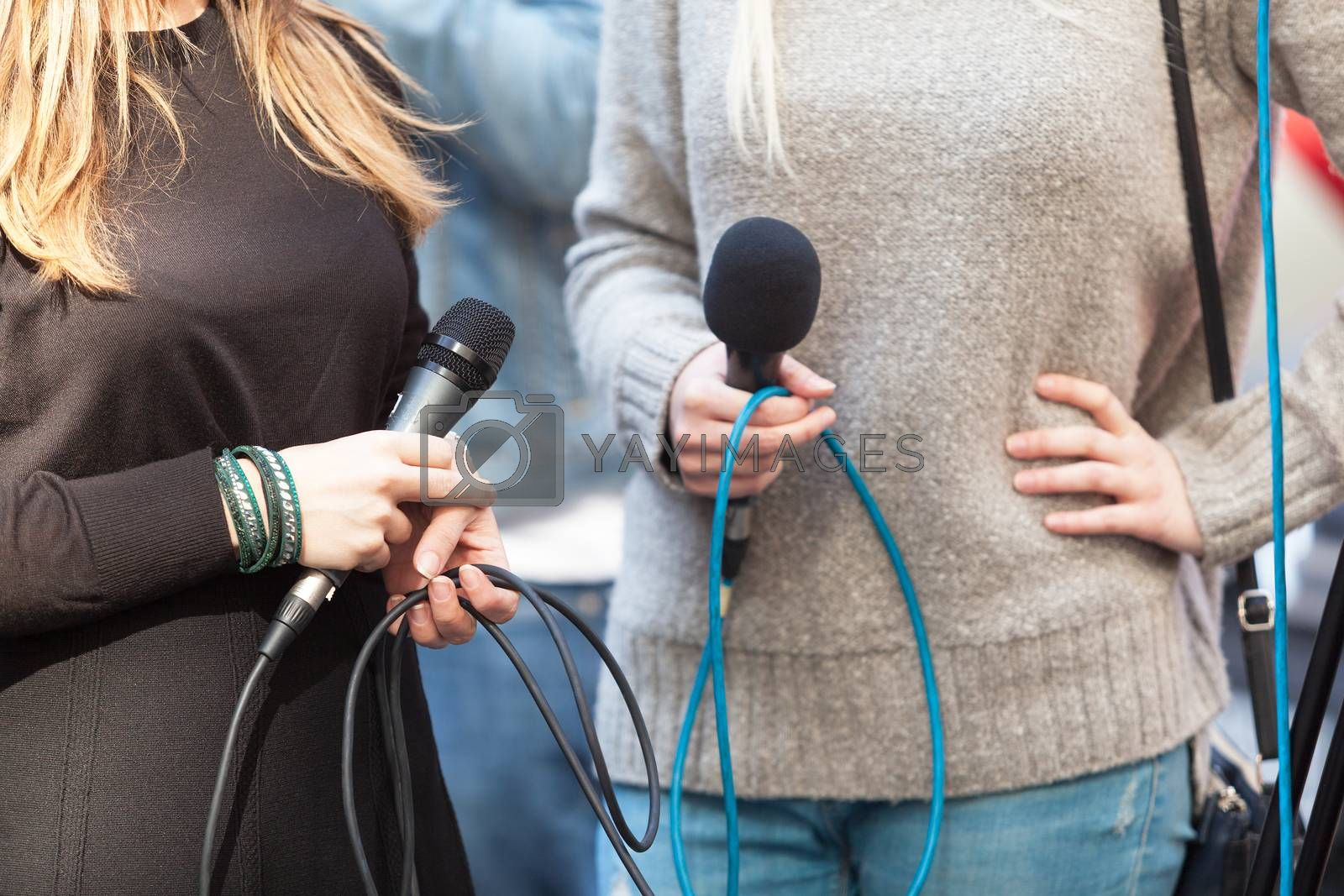 Female journalists holding microphones waiting for press conference