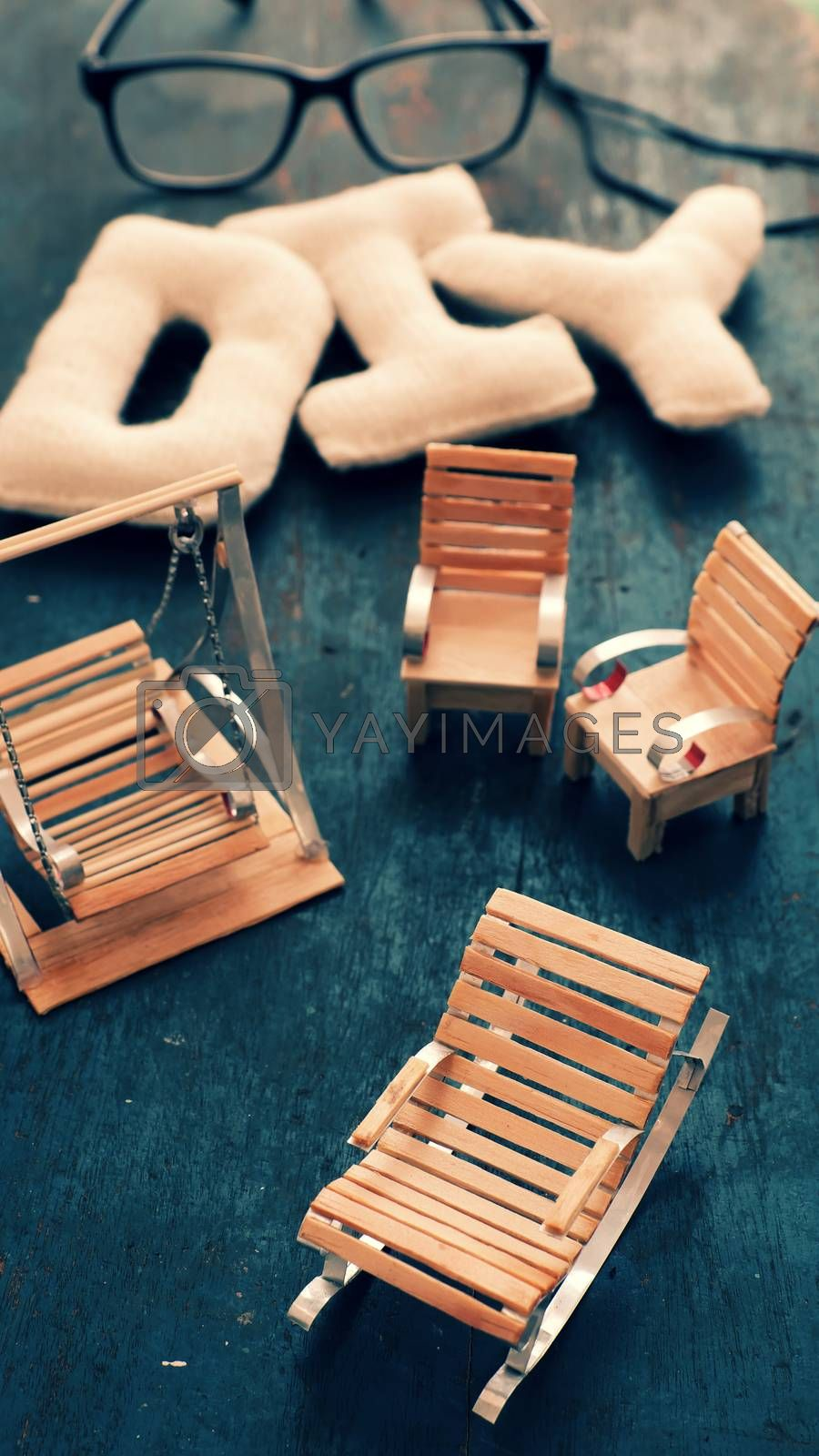 Amazing miniature handmade product for interior design, mini furniture make from wood stick on wooden background, small swing, chair so cute and diy knitted alphabet