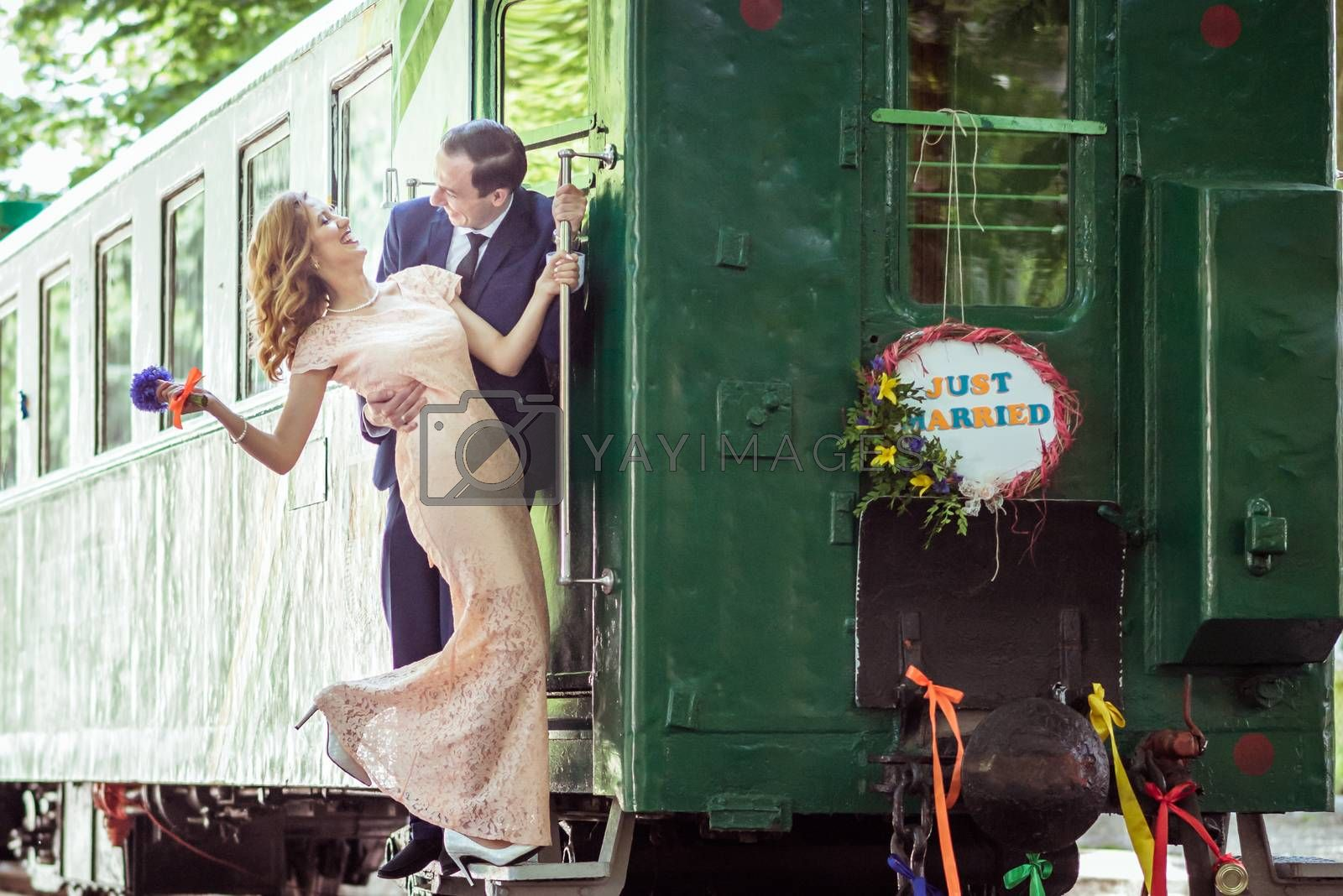 Just married happy couple on the ladder last wagon in Lviv, Ukraine
