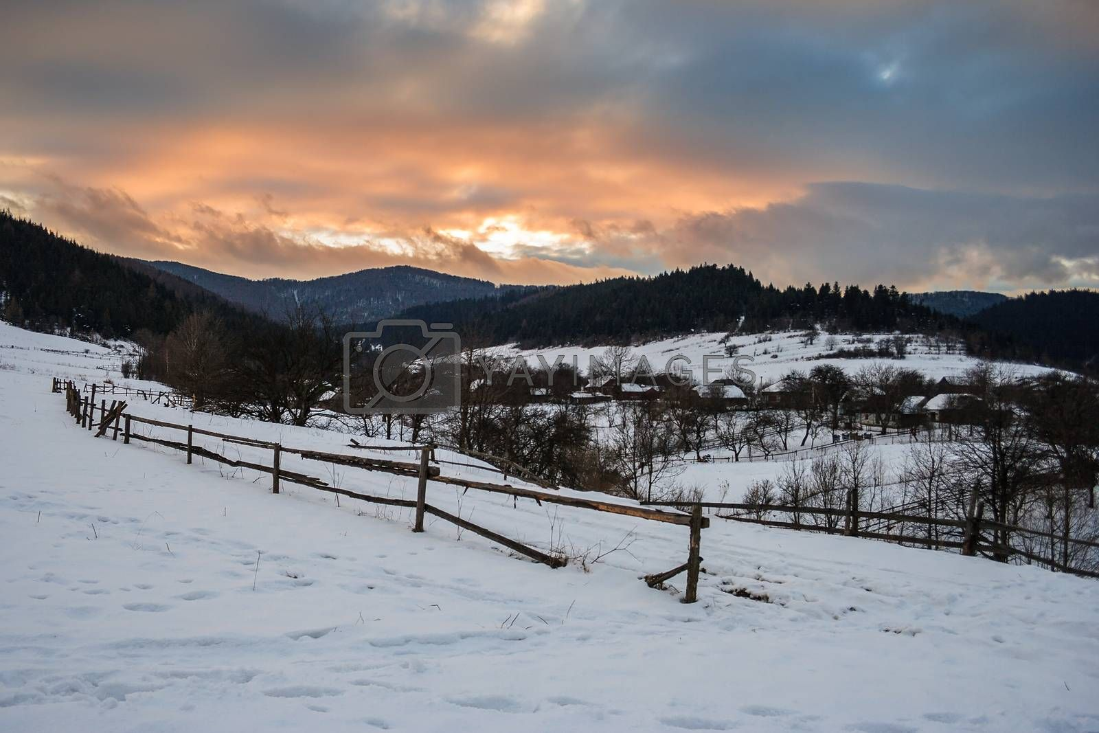 road to the village covered with snow in the mountains under a red winter sunset