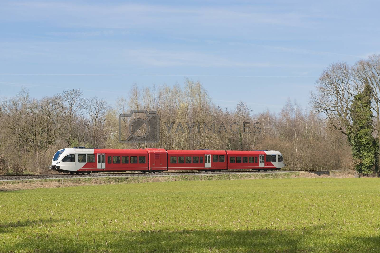 Red white colored train on a light rail track in the Achterhoek near Winterswijk in the Netherlands