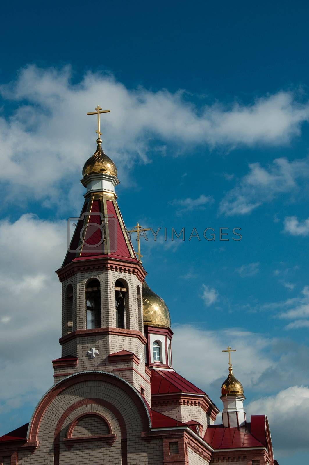 The dome of the Christian Church against the background of blue sky and white clouds